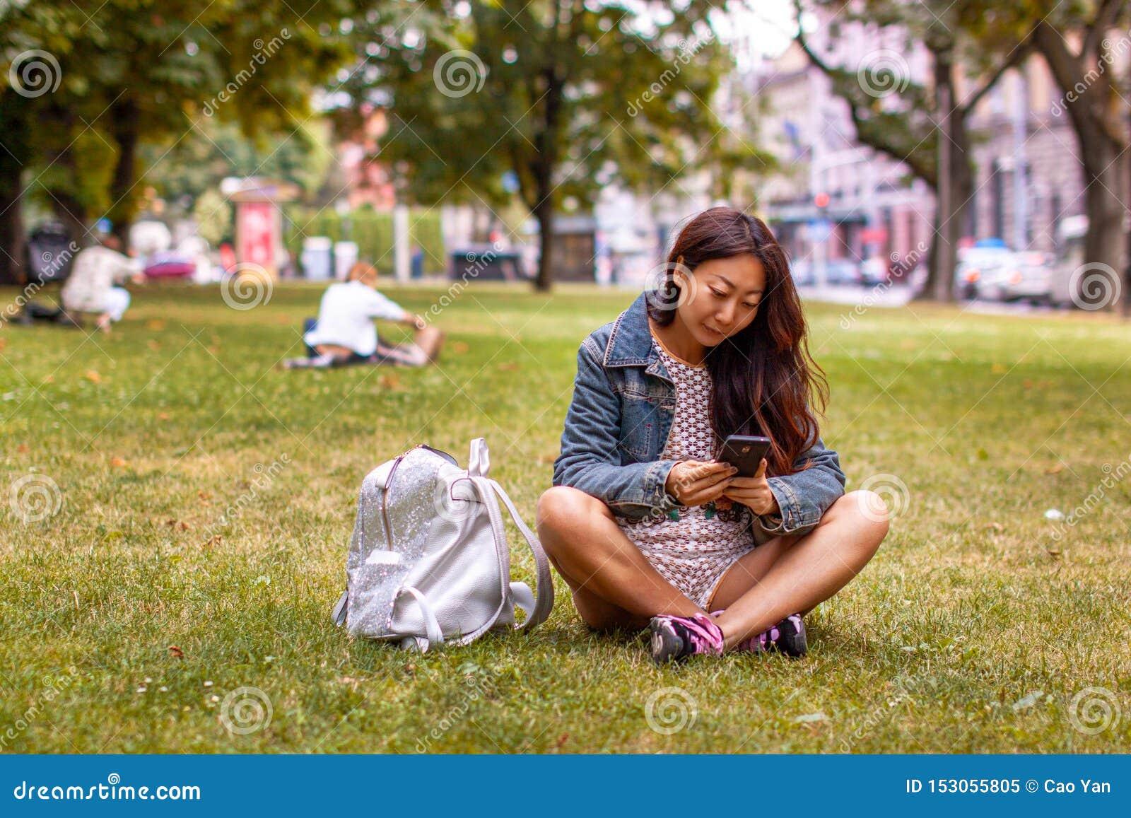Adolescente que coloca no parque usando o telefone m?vel