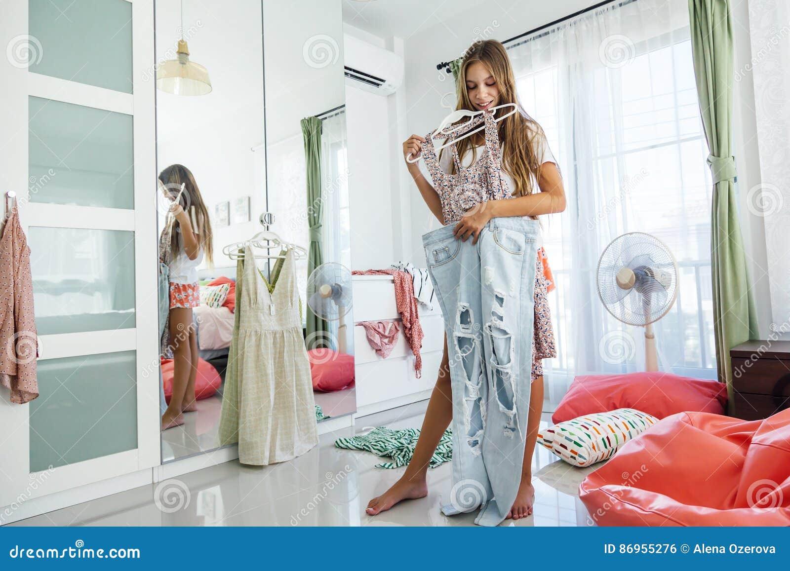 adolescente que elige la ropa en armario