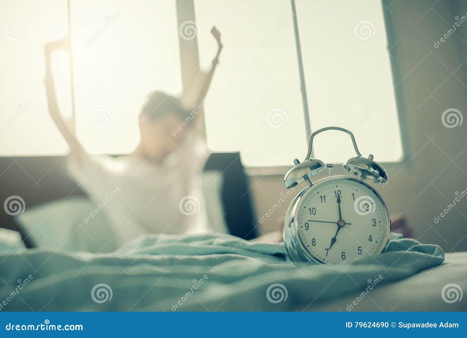 Adolescente que estica as mãos após a excitação na cama