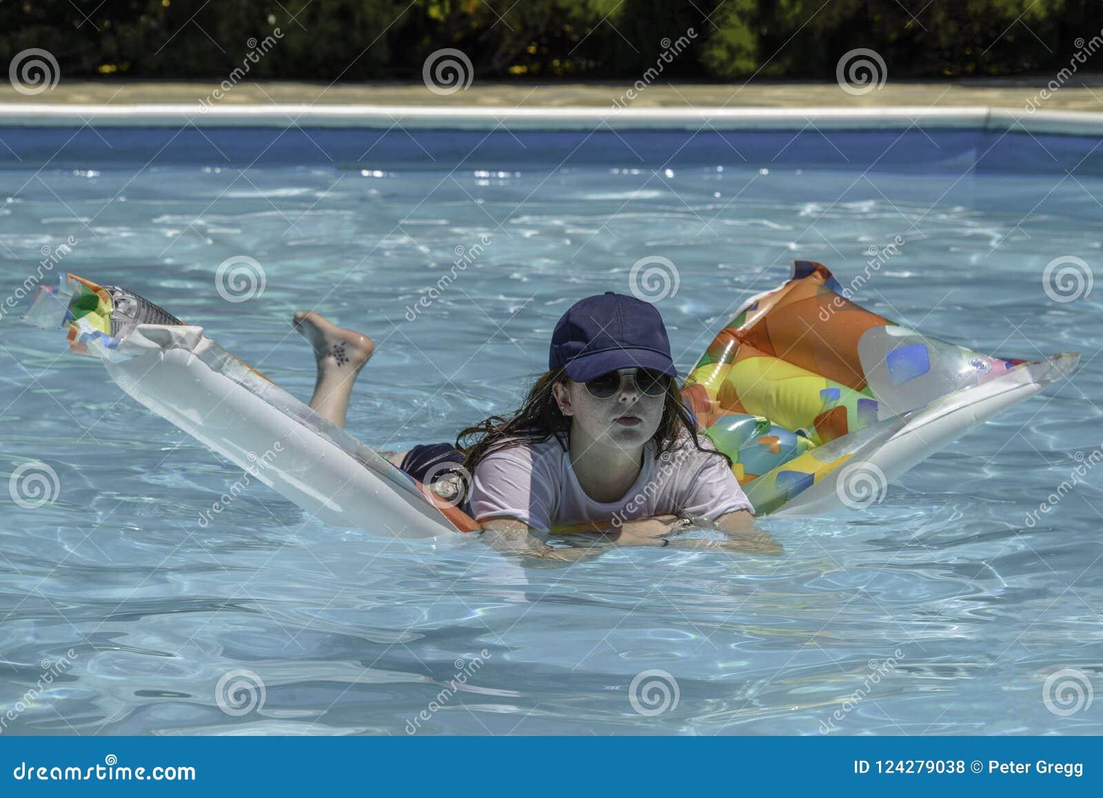 Adolescente que flota en un colchón neumático