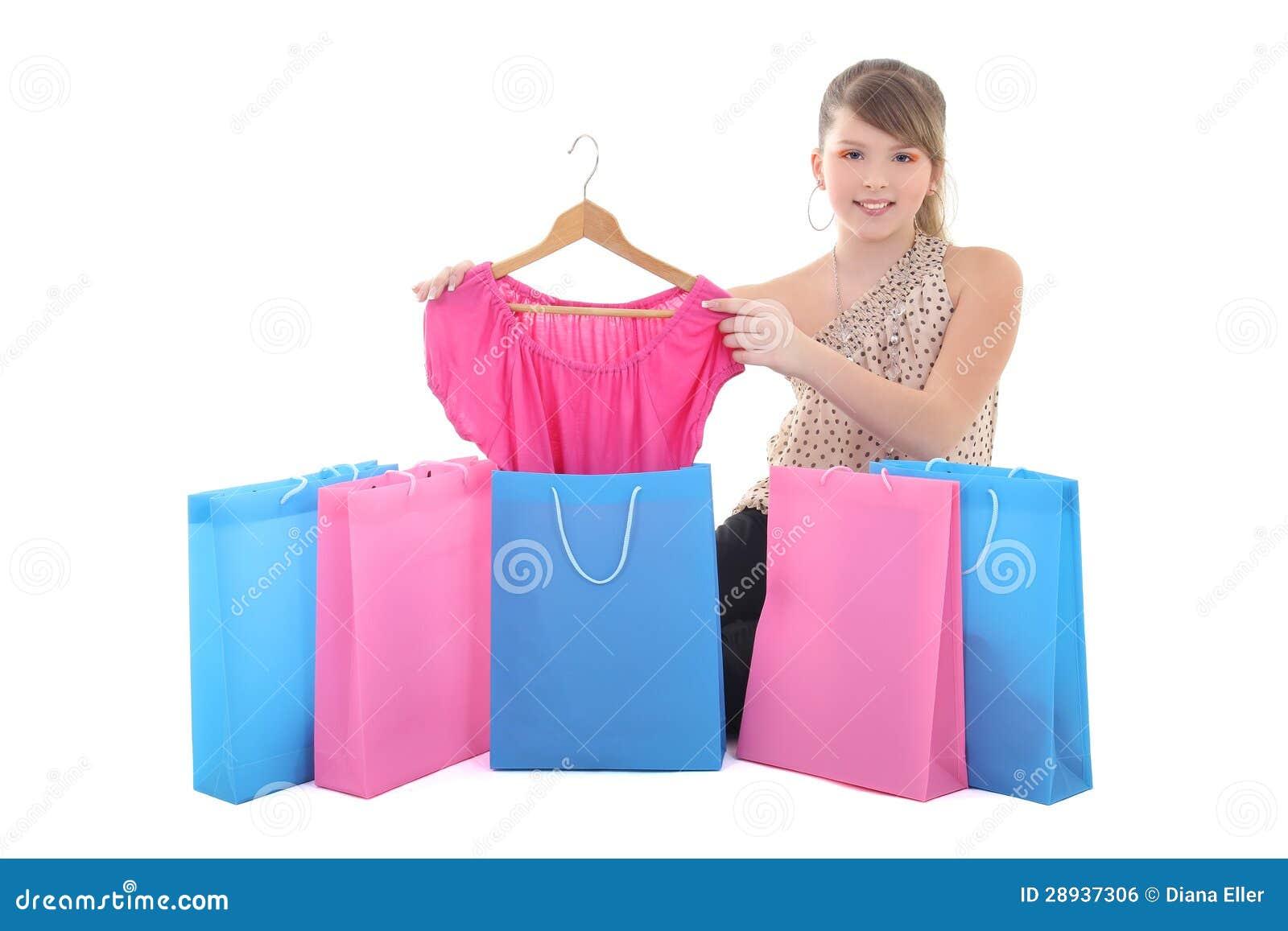 Adolescente que mostra o vestido novo com sacos de compras