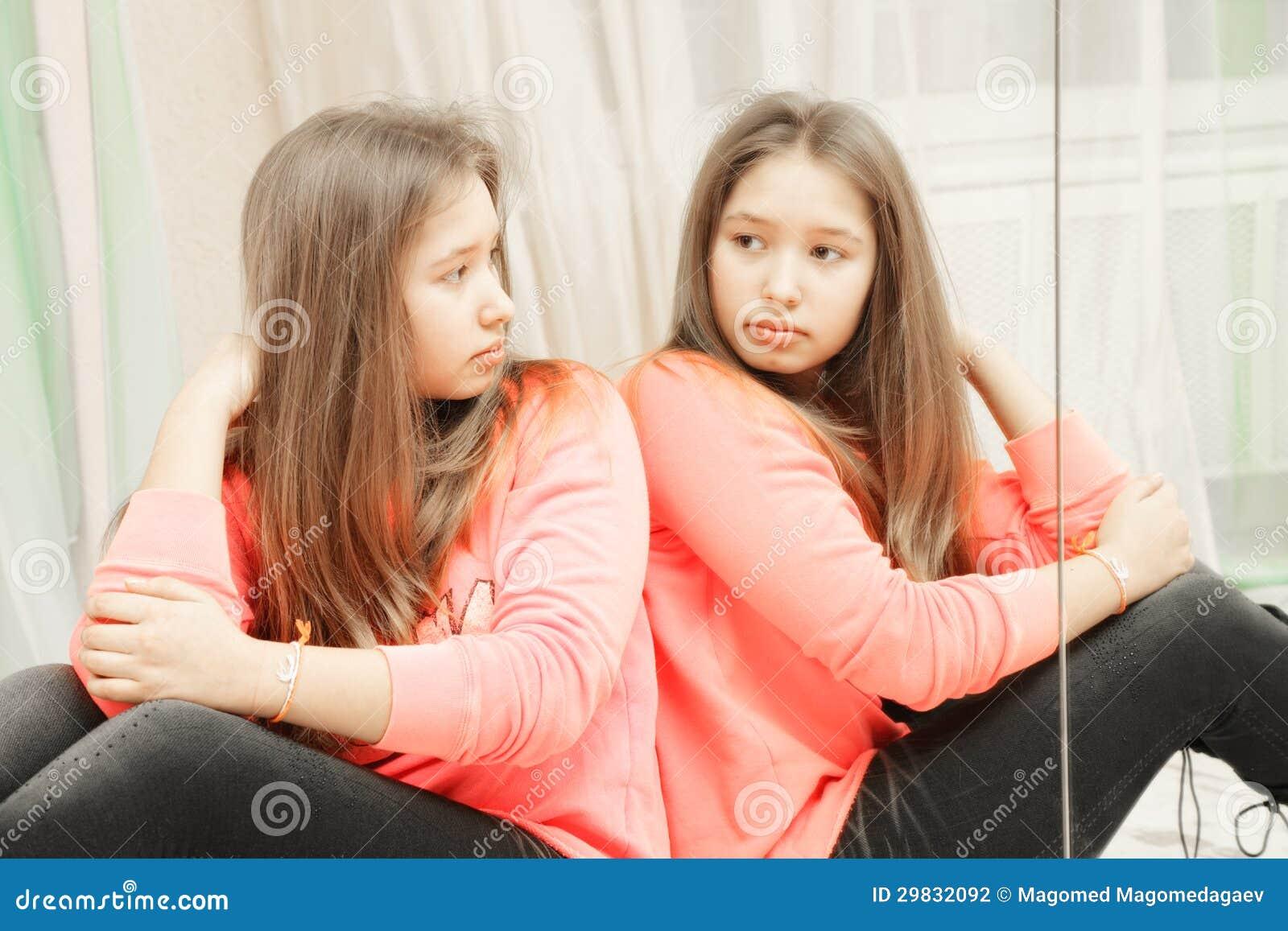 Adolescente que olha seu close up da reflexão