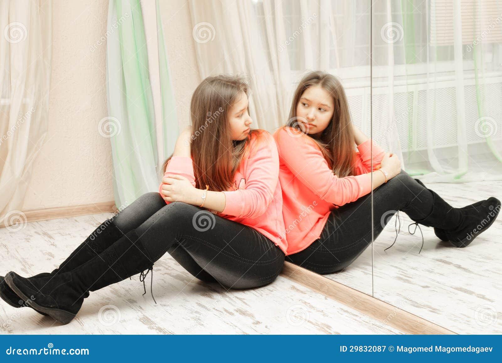 Adolescente que olha sua reflexão