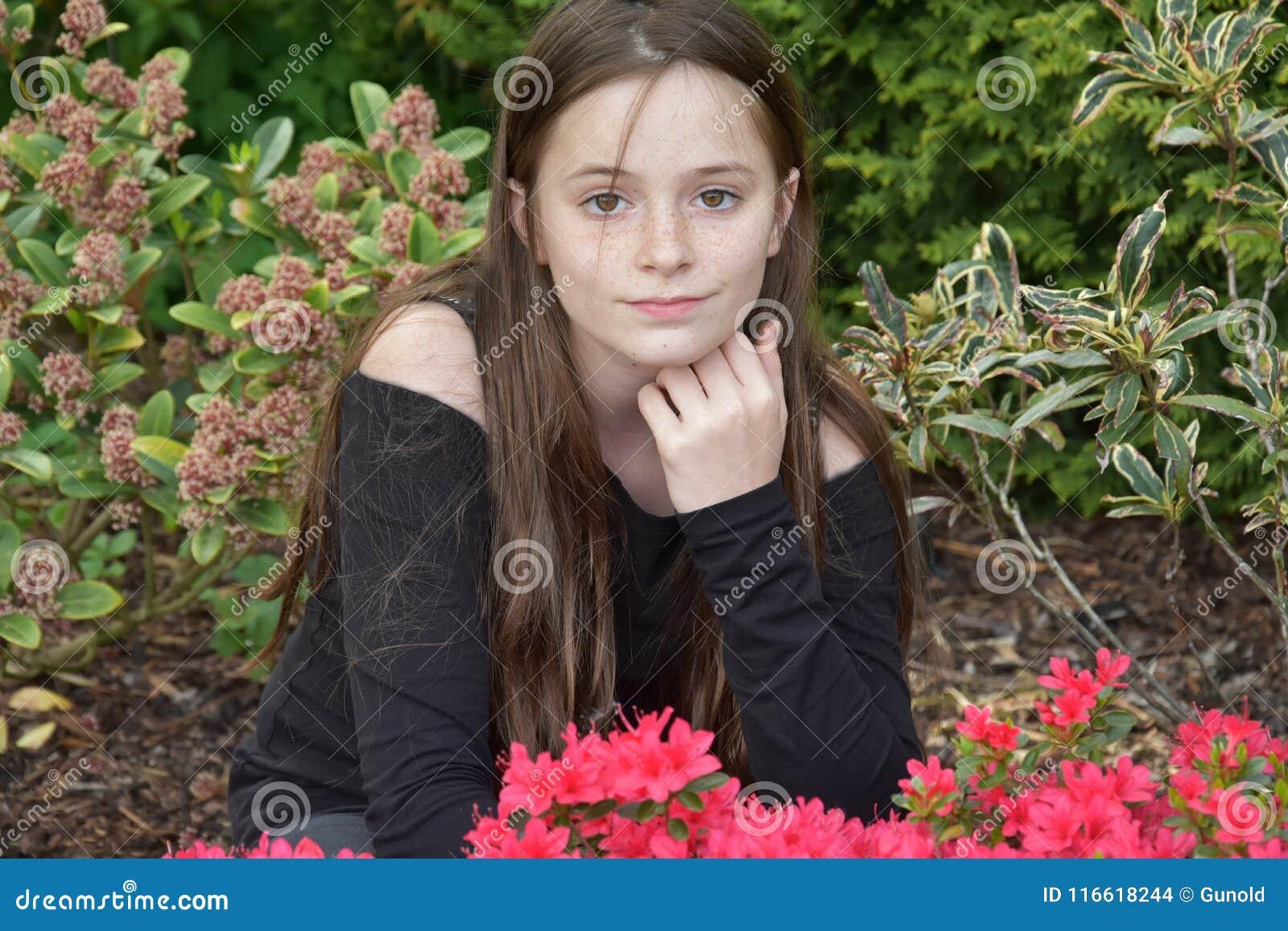 Adolescente que presenta para las fotos en el jardín