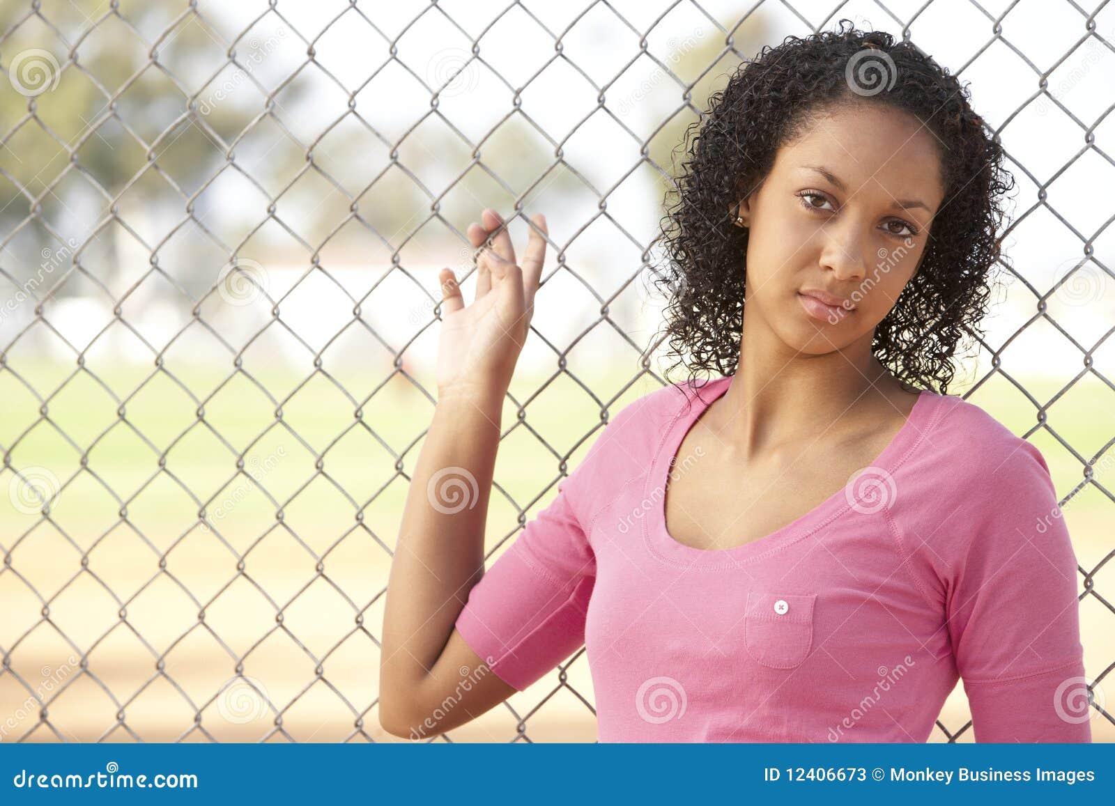 Adolescente que senta-se no campo de jogos