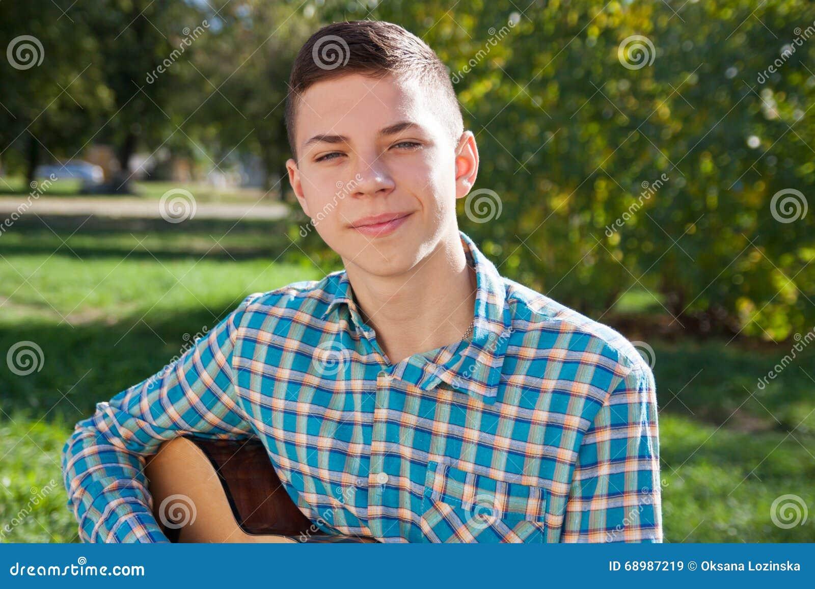 Adolescente que toca la guitarra en la naturaleza