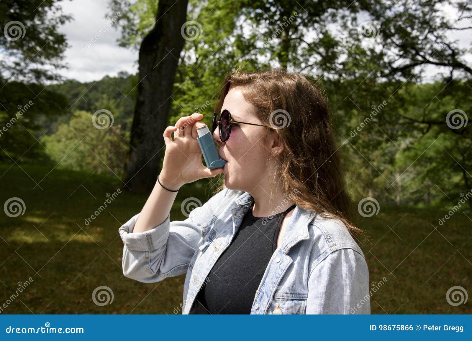 Adolescente que usa a paisagem do inalador