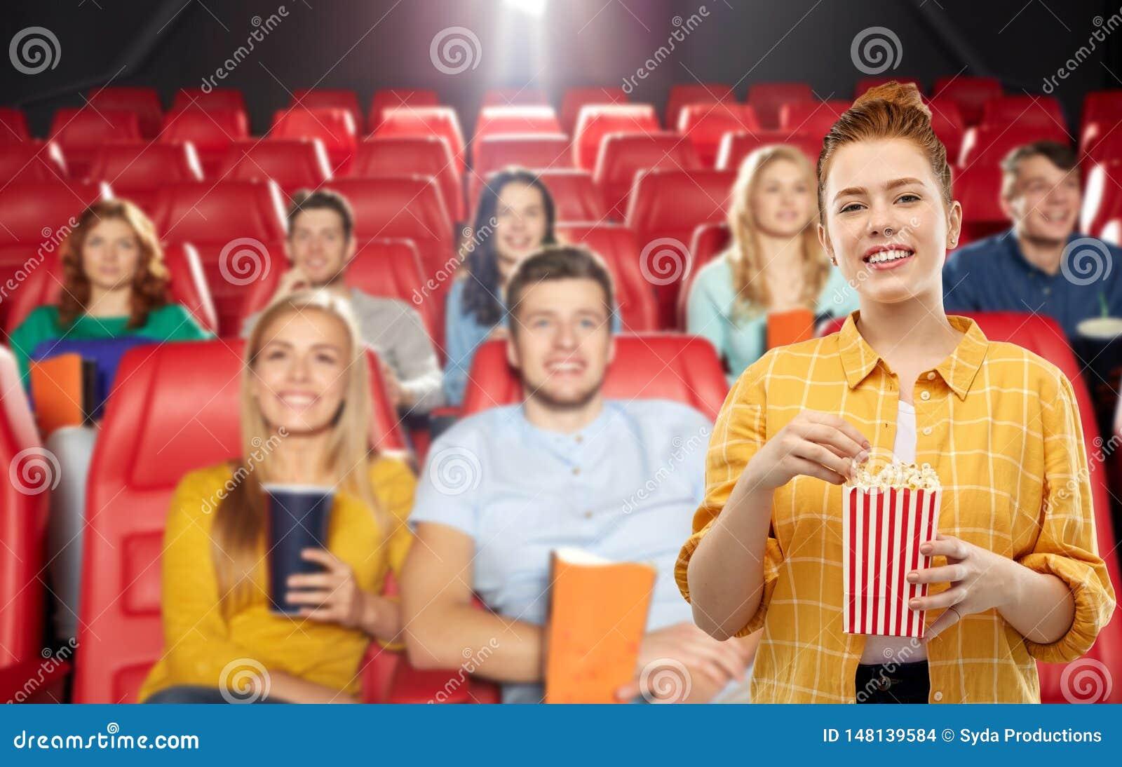 Adolescente rousse avec le maïs éclaté à la salle de cinéma