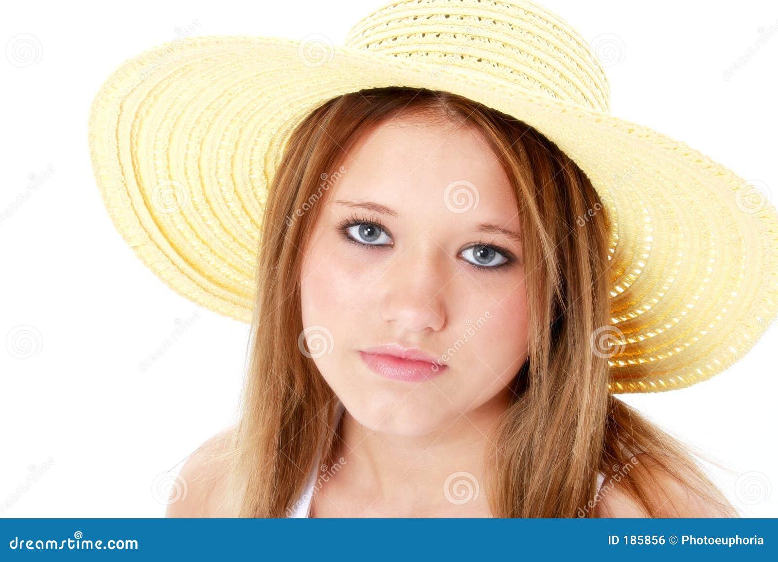 Adolescente serio hermoso en sombrero amarillo sobre blanco