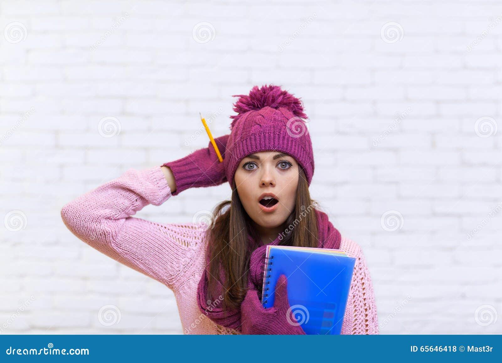 Adolescente stunned attirante dans le crayon rose de Shocked Holding Folder d étudiant de chapeau