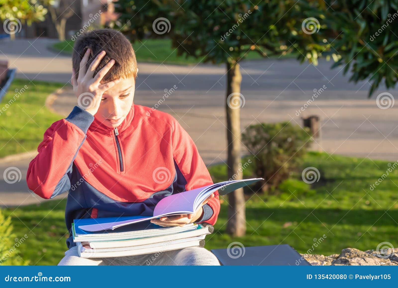 Adolescente triste virado com livros de texto e cadernos
