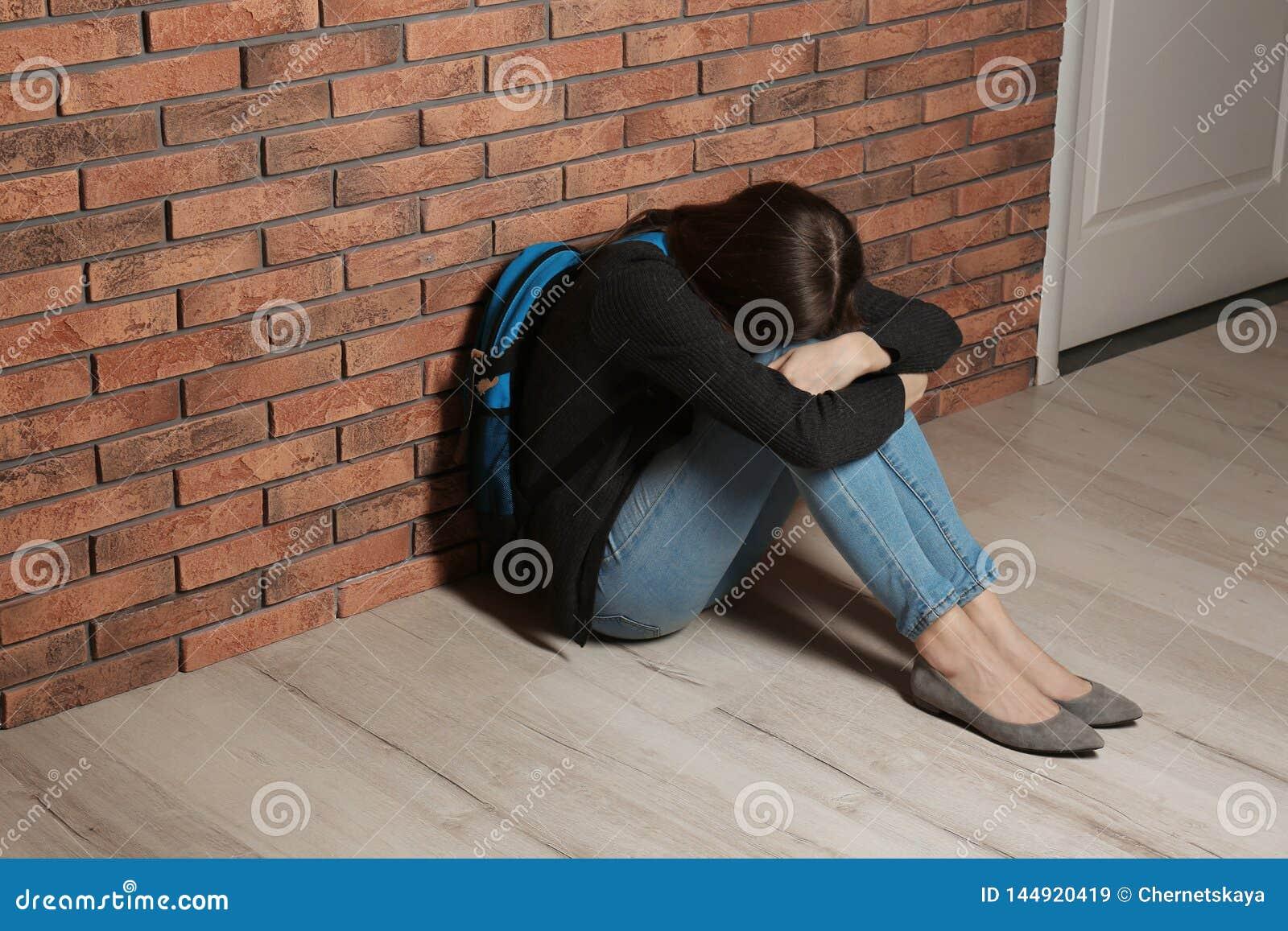 Adolescente turbato con lo zaino che si siede sul pavimento vicino alla parete