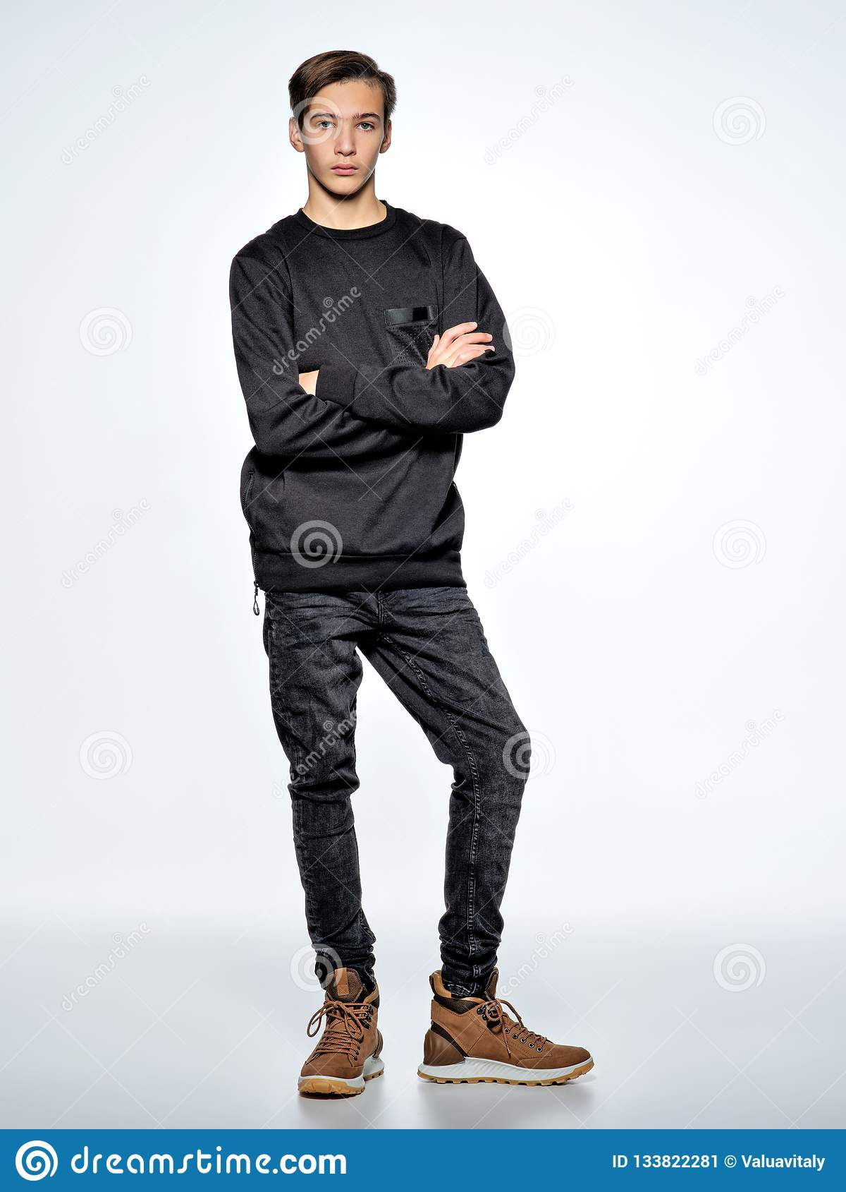 Adolescente vestido en la ropa de moda negra que presenta en el estudio