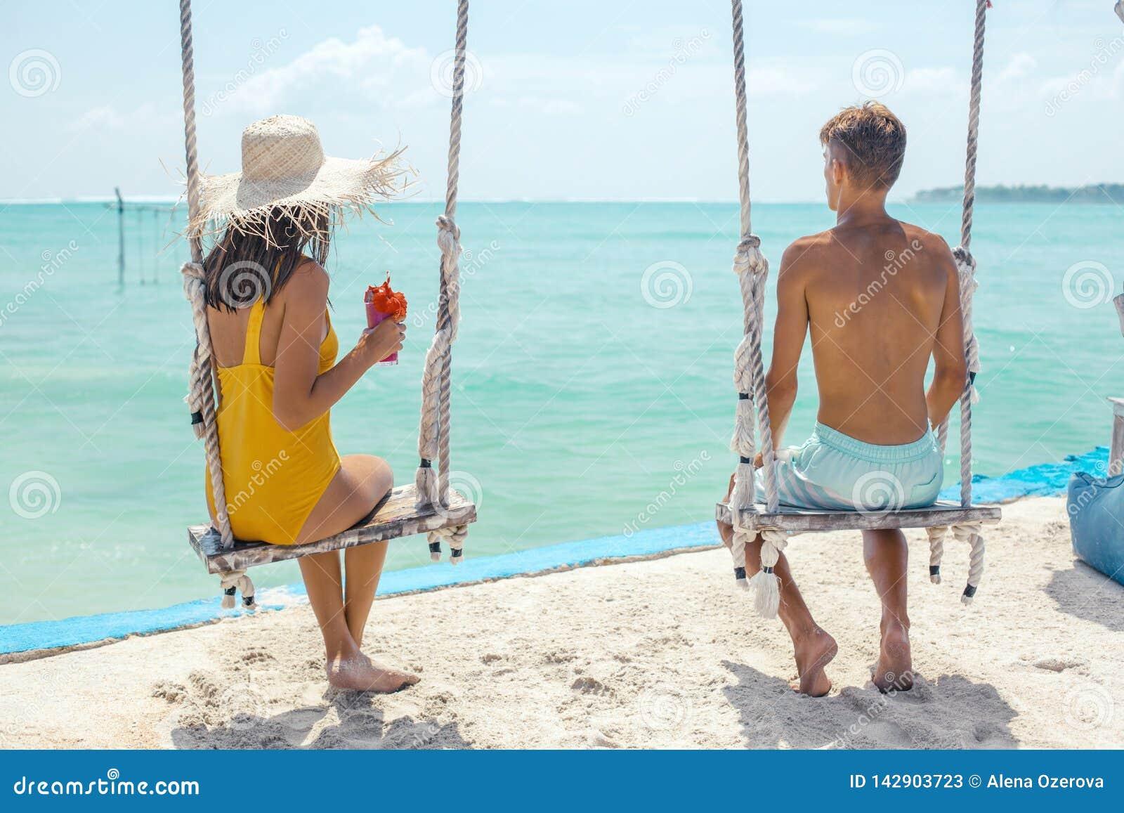 Adolescente y muchacho que cuelgan en oscilaciones con una opinión del mar en café de la playa