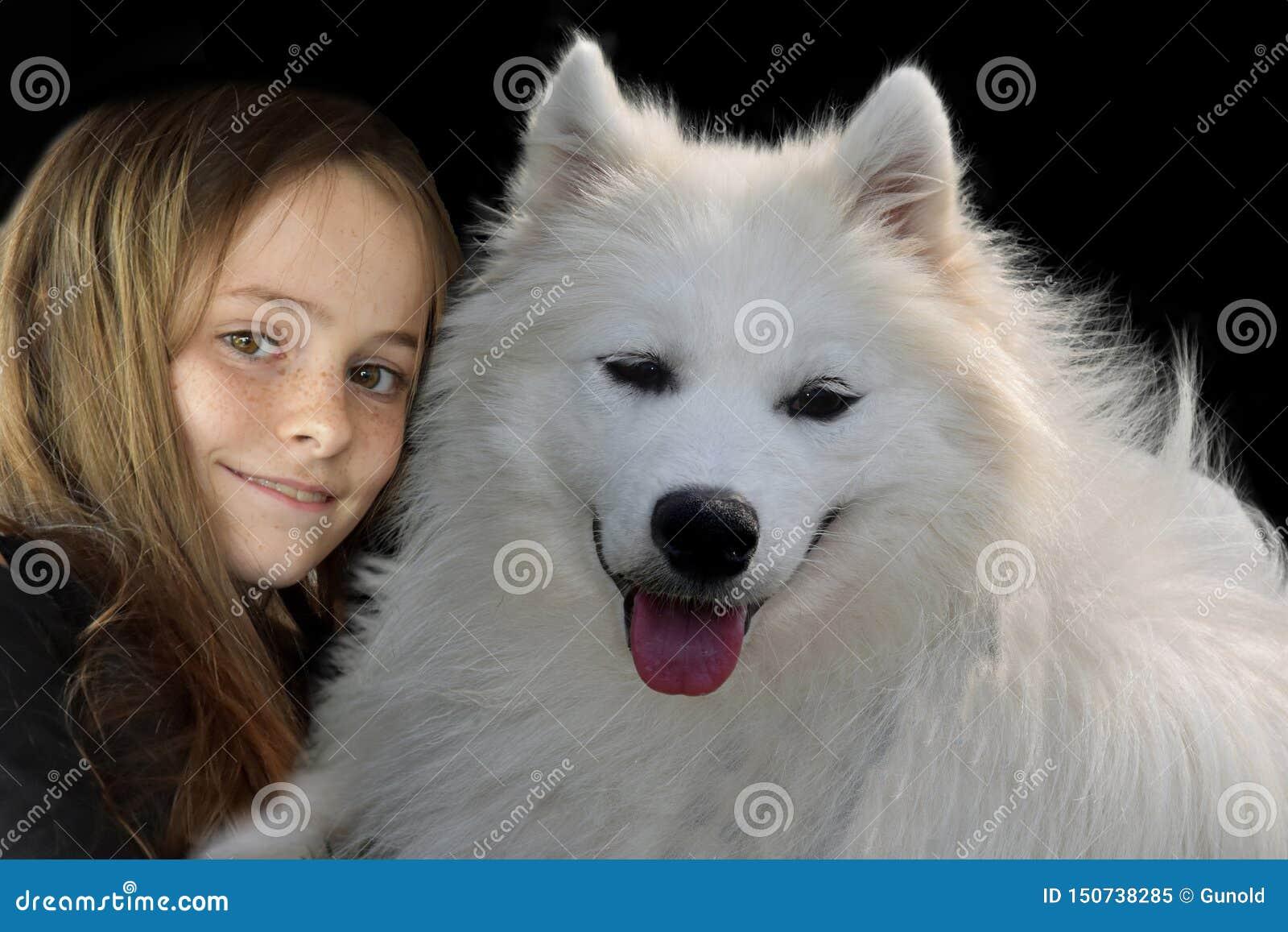 Adolescente y su perro del samoyedo