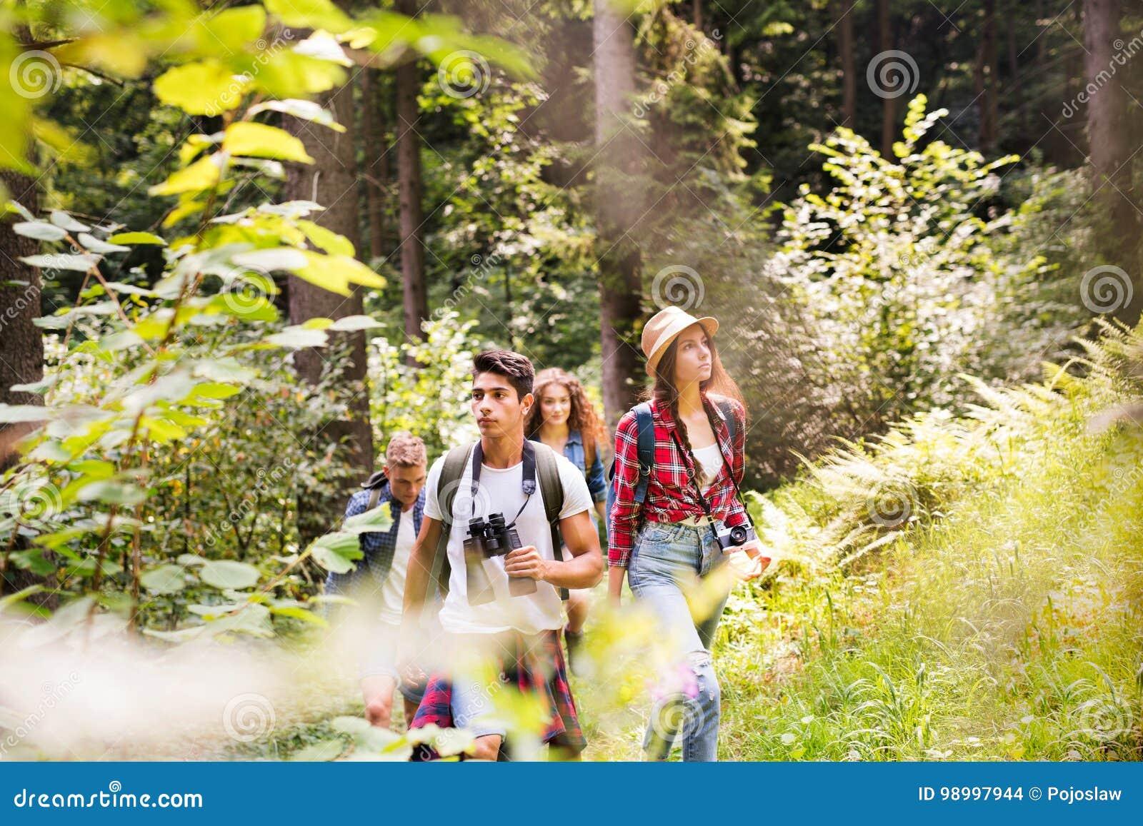 Adolescentes con las mochilas que caminan en vacaciones de verano del bosque