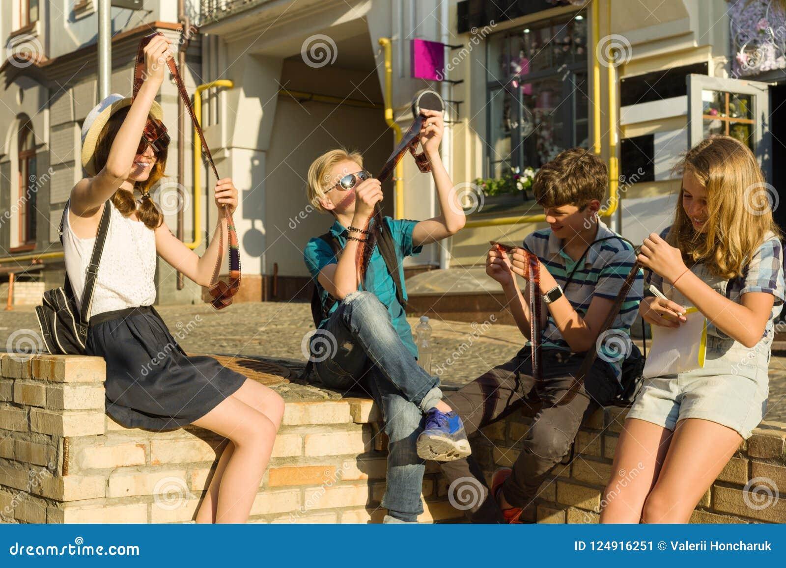 Adolescentes con las negativas de observación de la foto de la película del interés y de la sorpresa, fondo de la calle de la ciu