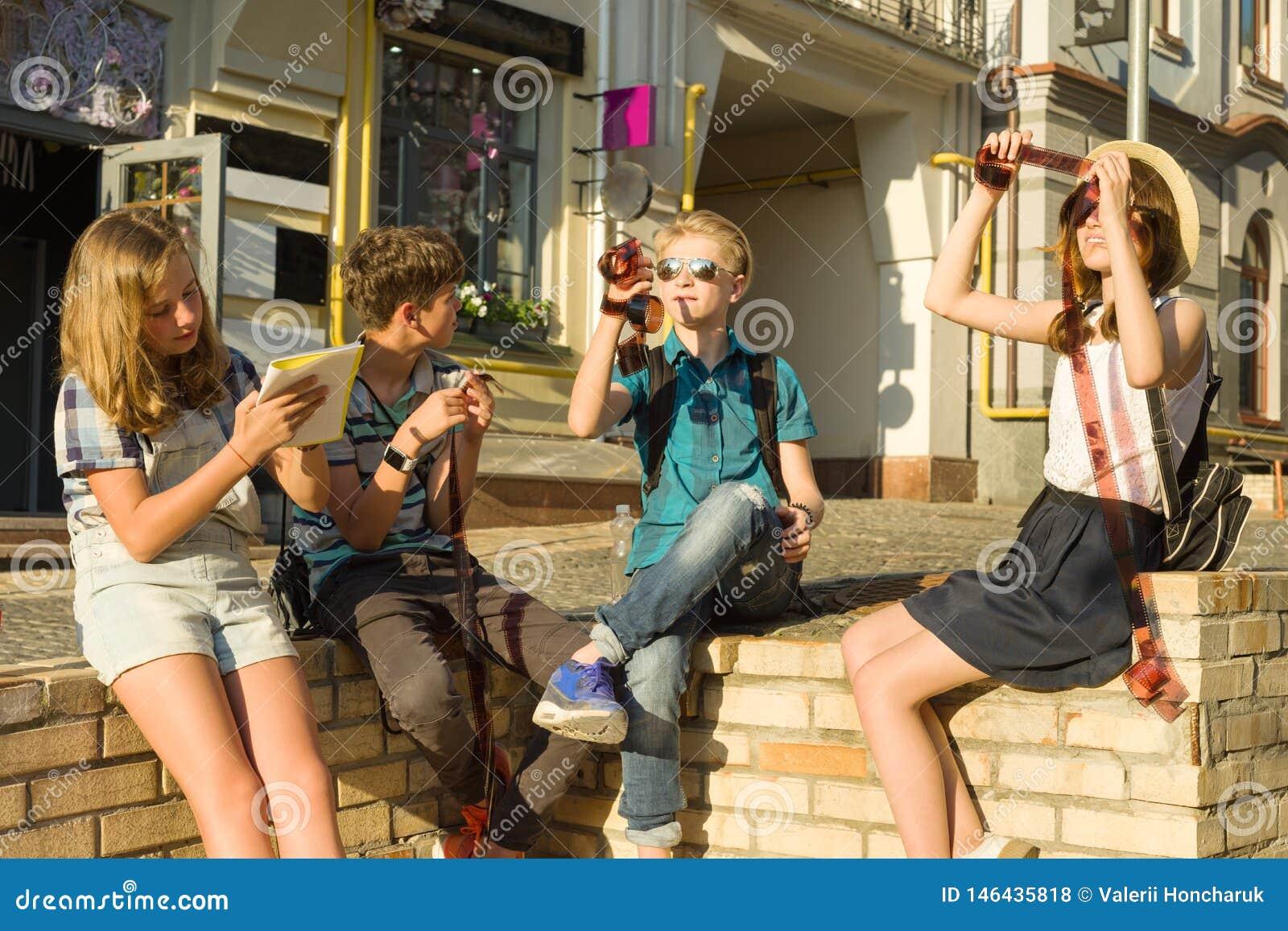 Adolescentes con las negativas de observaci?n de la foto de la pel?cula del inter?s y de la sorpresa, fondo de la calle de la ciu