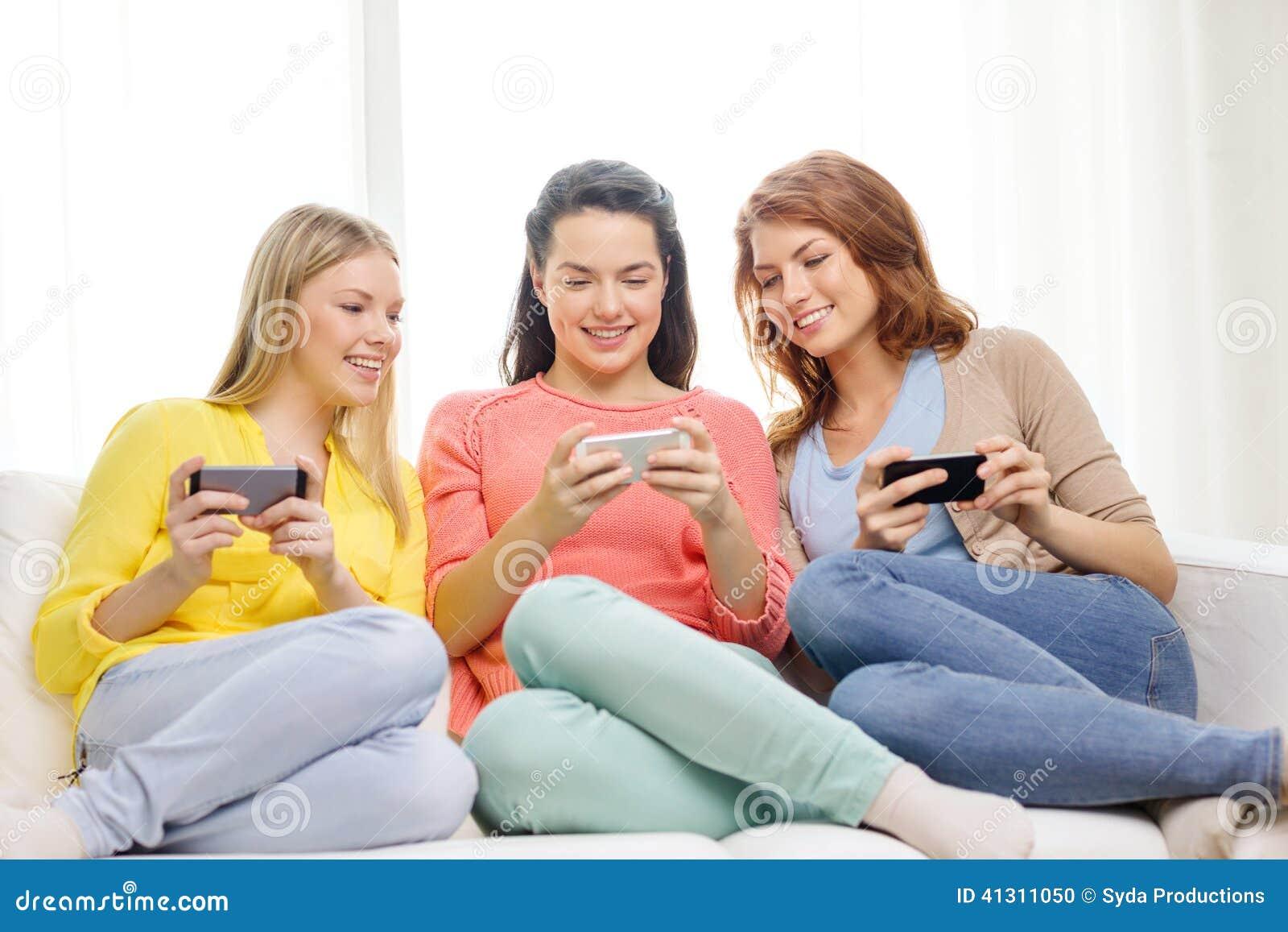 Adolescentes de sorriso com smartphones em casa
