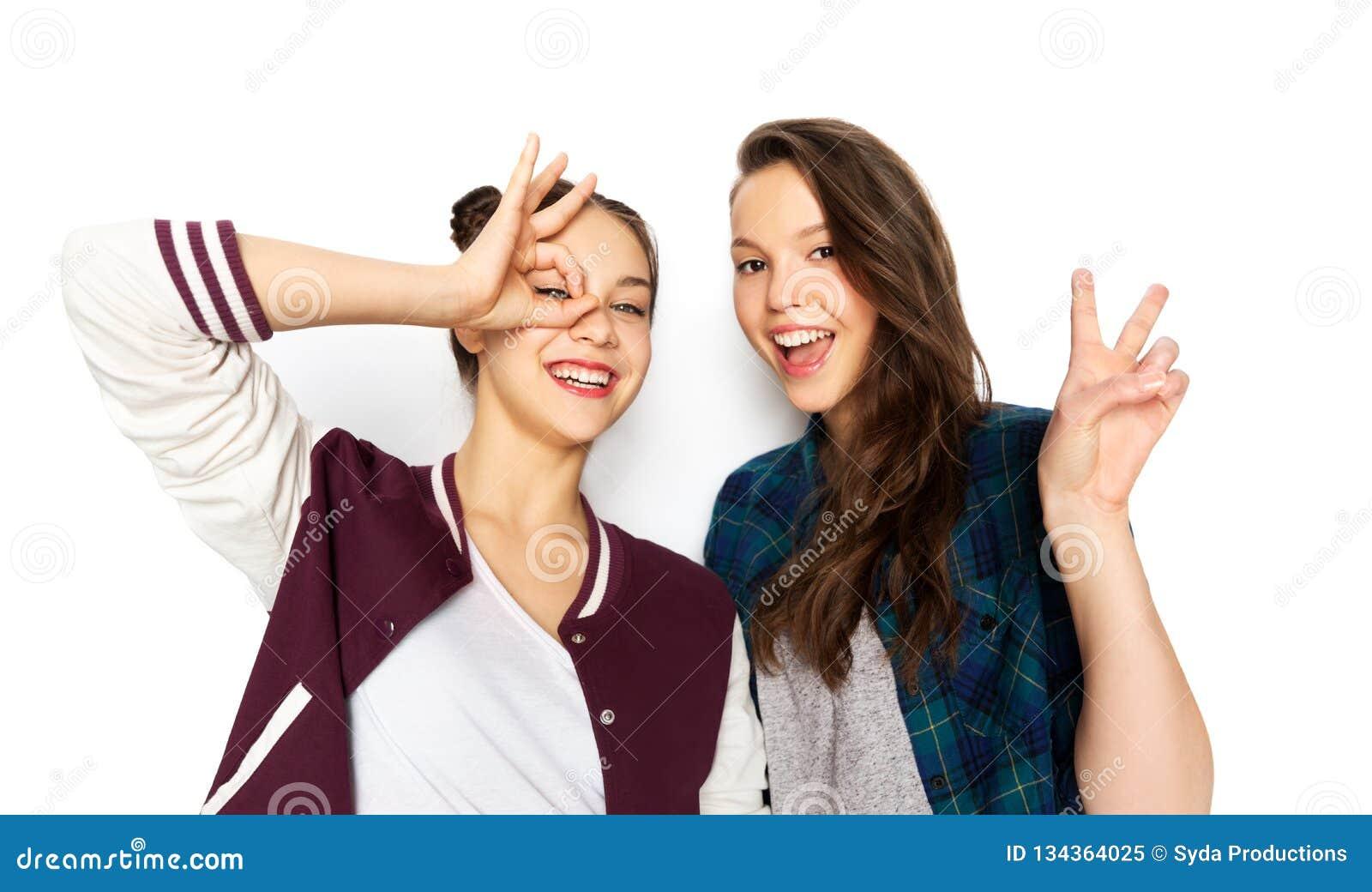 Adolescentes de sorriso felizes que fazem gestos