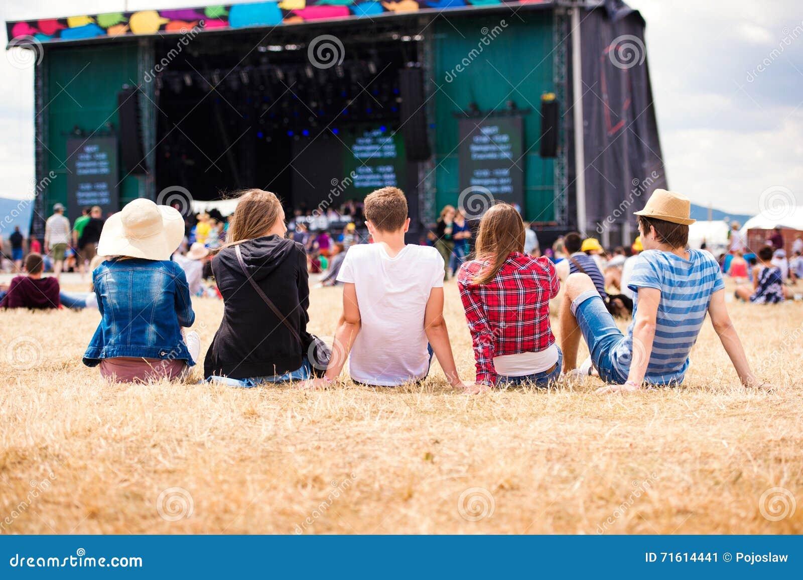Adolescentes, festival de música do verão, sentando-se na frente da fase