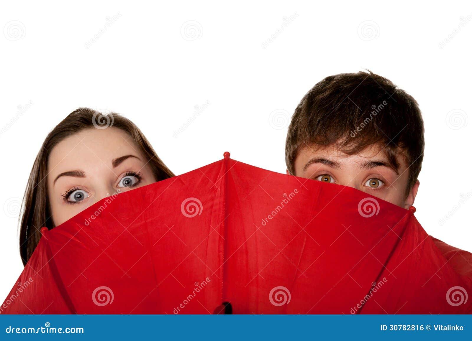 Adolescentes, muchacho y muchacha, mirando furtivamente para el paraguas rojo.