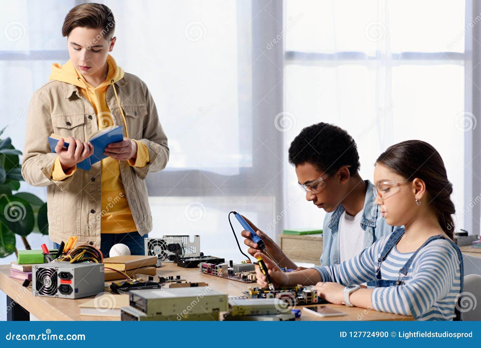 Adolescentes multiculturais que soldam o circuito de computador com ferro e amigo de solda