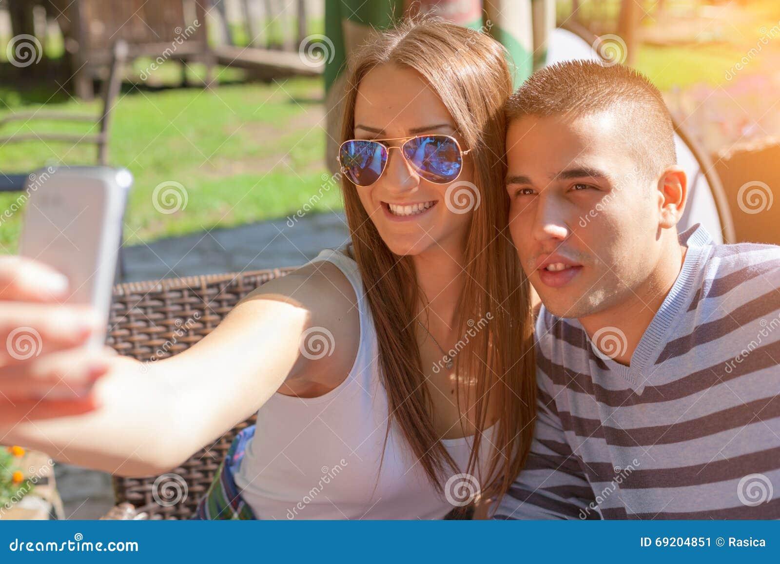 Adolescentes novos dos pares que sorriem e que tomam o selfie fora