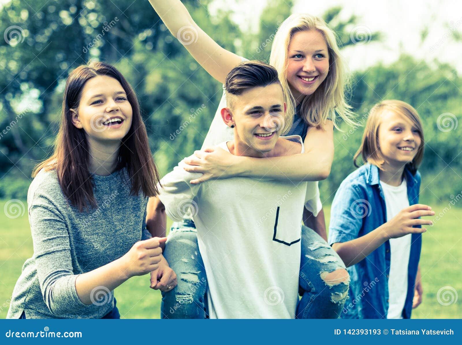 Adolescentes que corren a través de césped verde en verano en parque