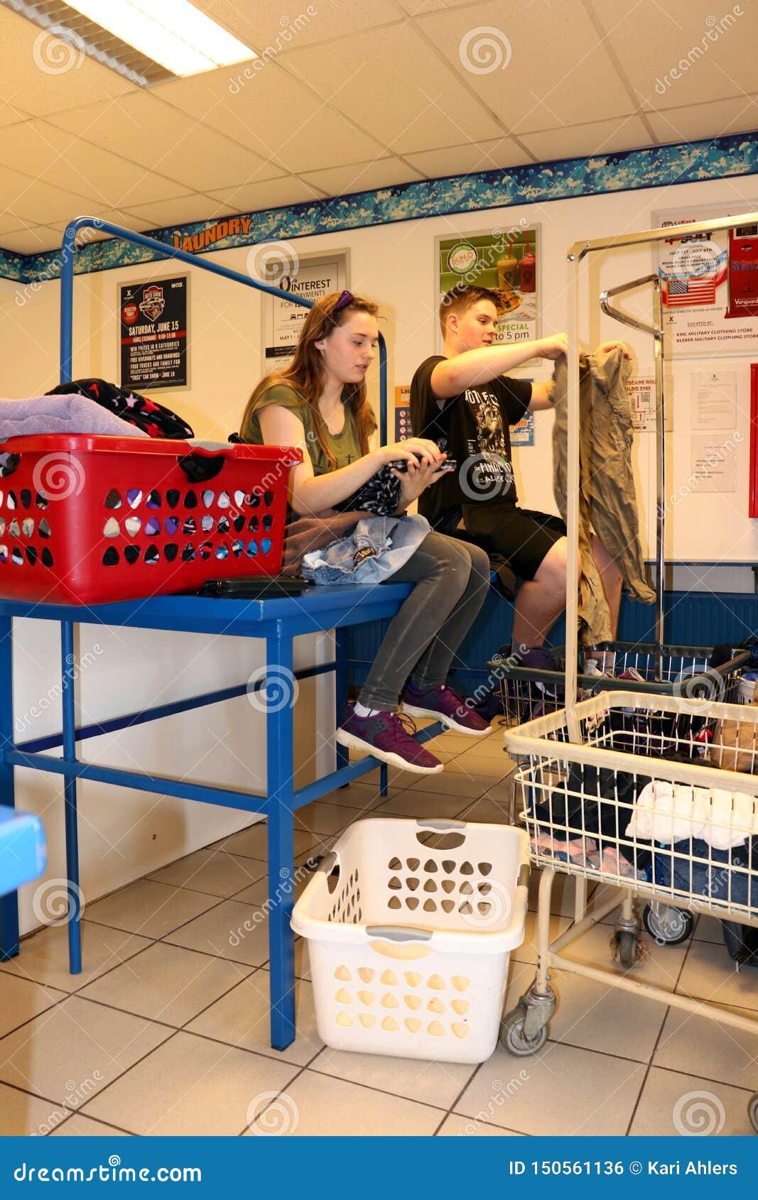 Adolescentes que dobram a roupa em uma lavagem automática