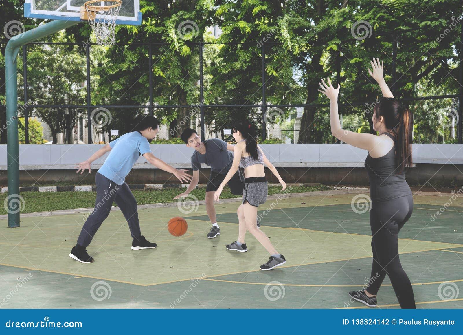 Adolescentes que jogam o basquetebol junto no ar livre