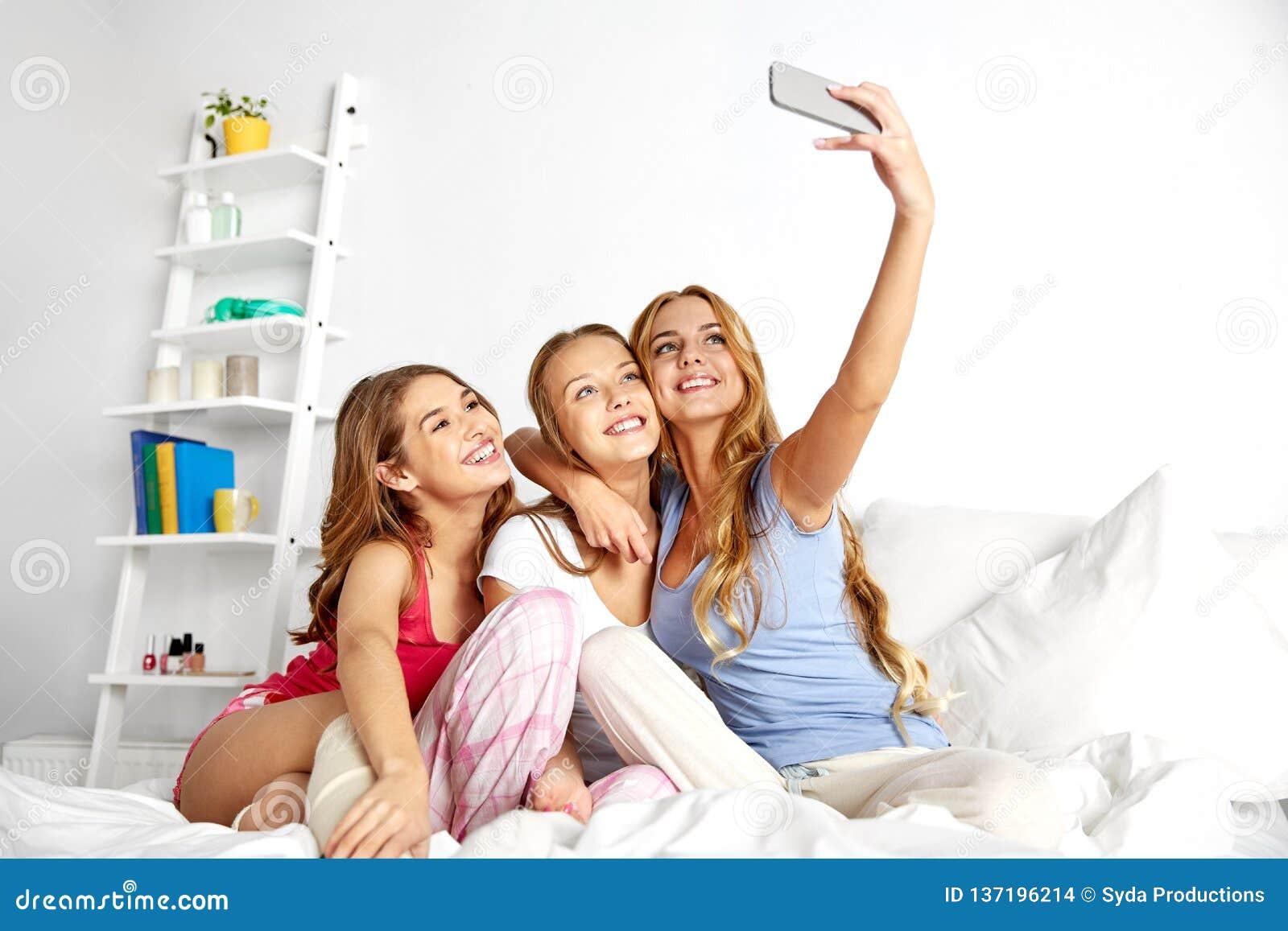 Adolescentes que tomam o selfie pelo smartphone em casa