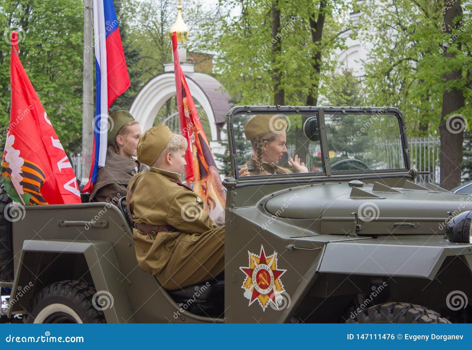Adolescentes sob a forma de um soldado do russo em um carro militar