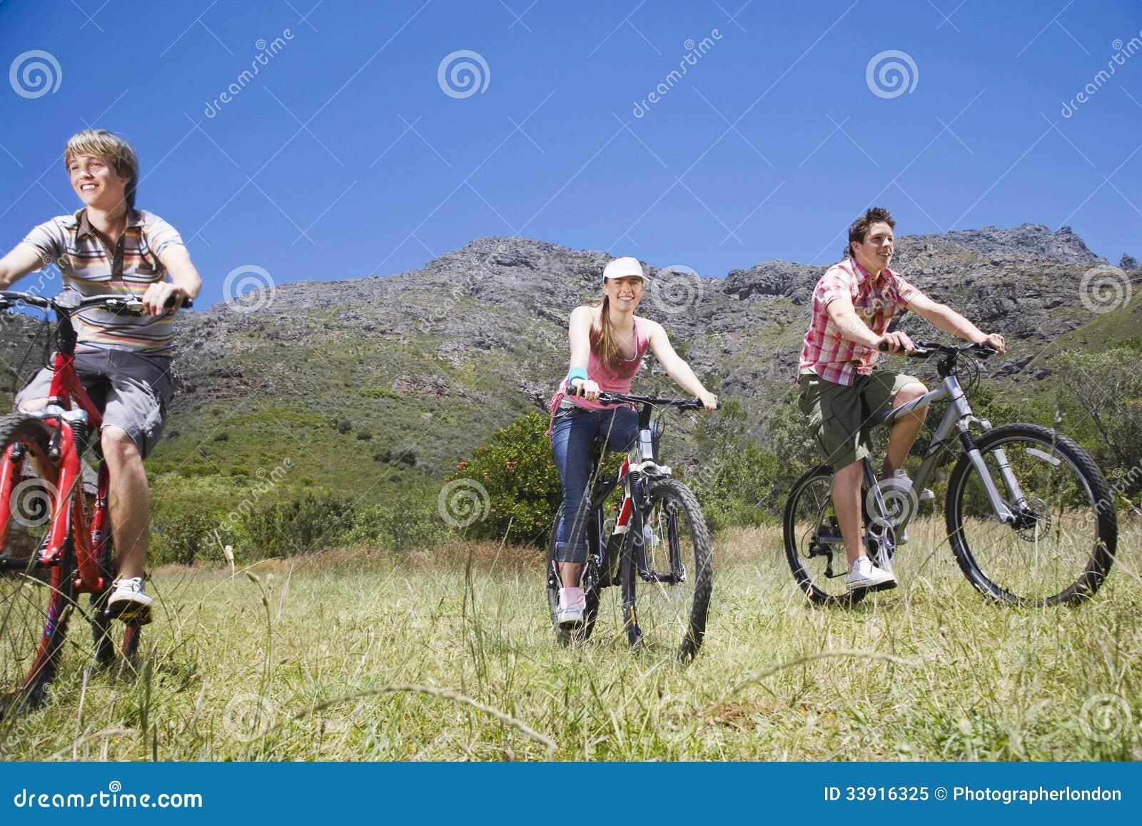 Adolescentes y muchacha Biking al aire libre
