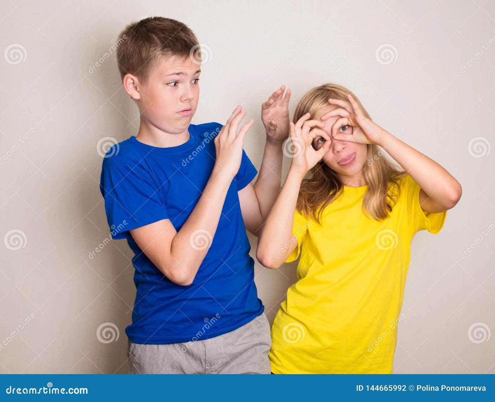 Adolescenti che hanno divertimento Ragazzo e ragazza che fanno lo smorfia divertente dei fronti La gente, amici, anni dell adoles