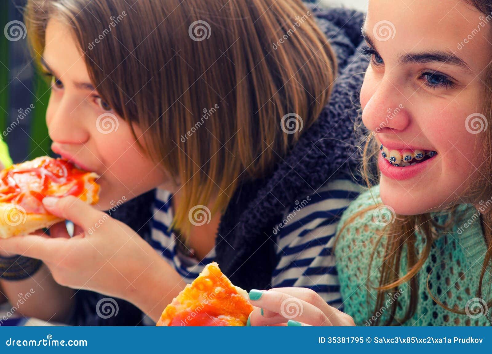 Adolescenti che mangiano pizza