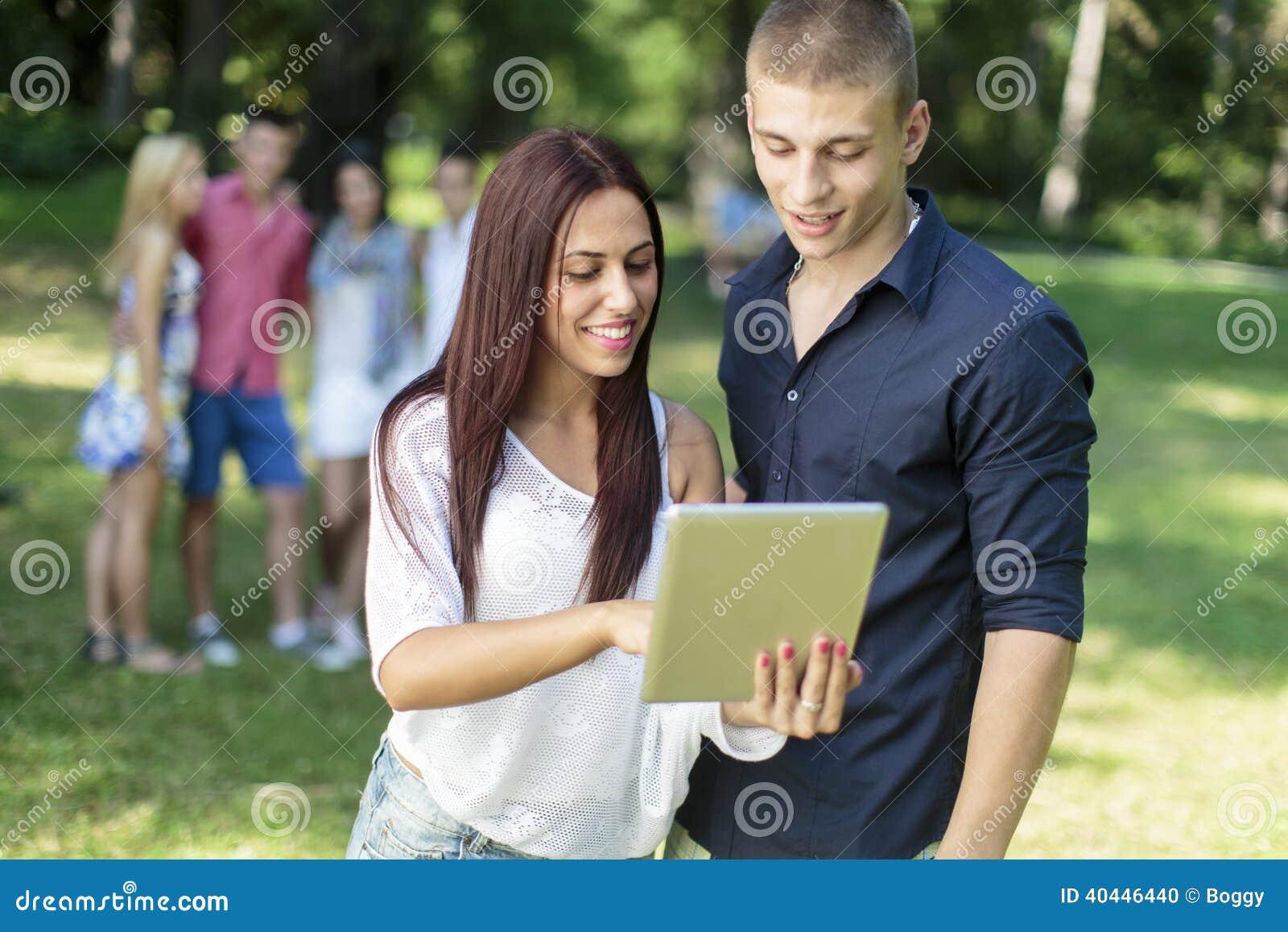 Adolescenti con la compressa in parco