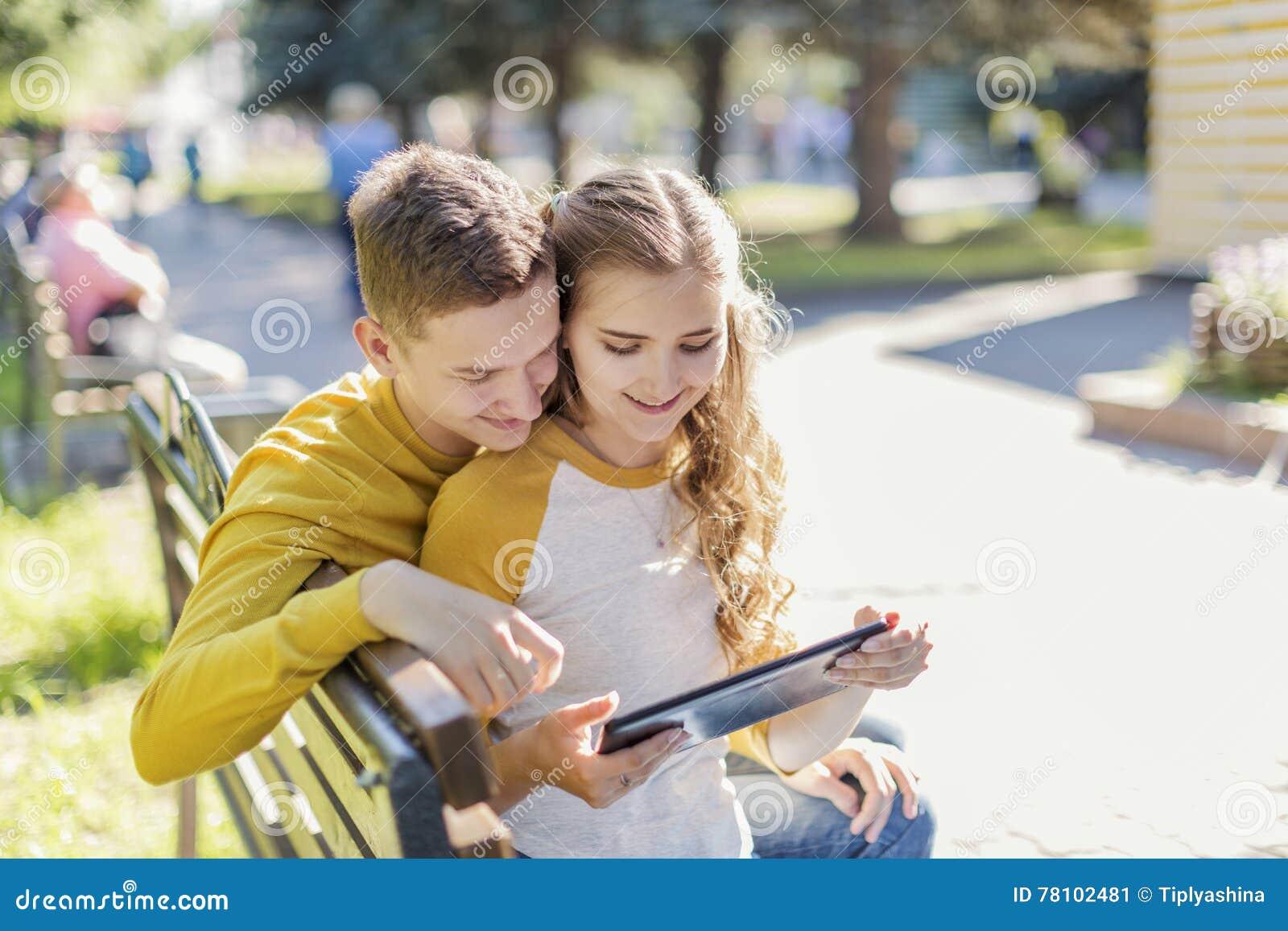 Adolescenti delle coppie su un banco