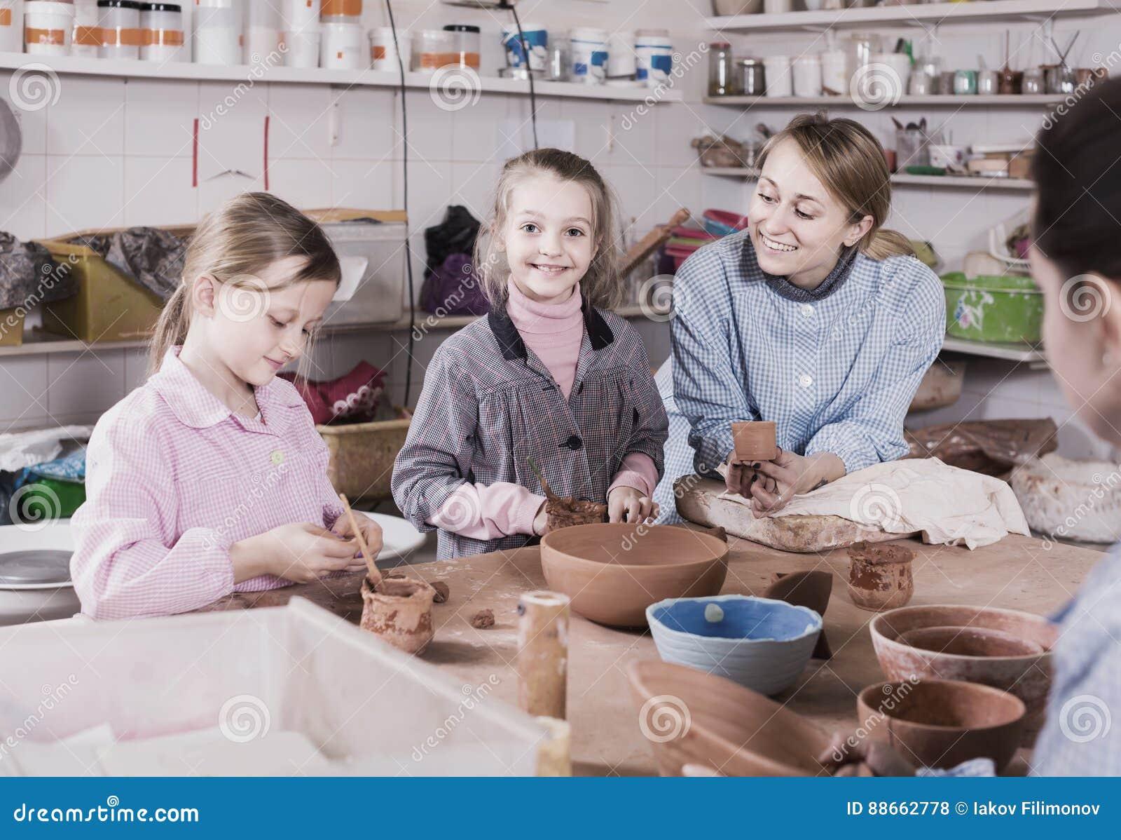 Adolescents de aide de professeur à faire la poterie pendant les arts et le craf