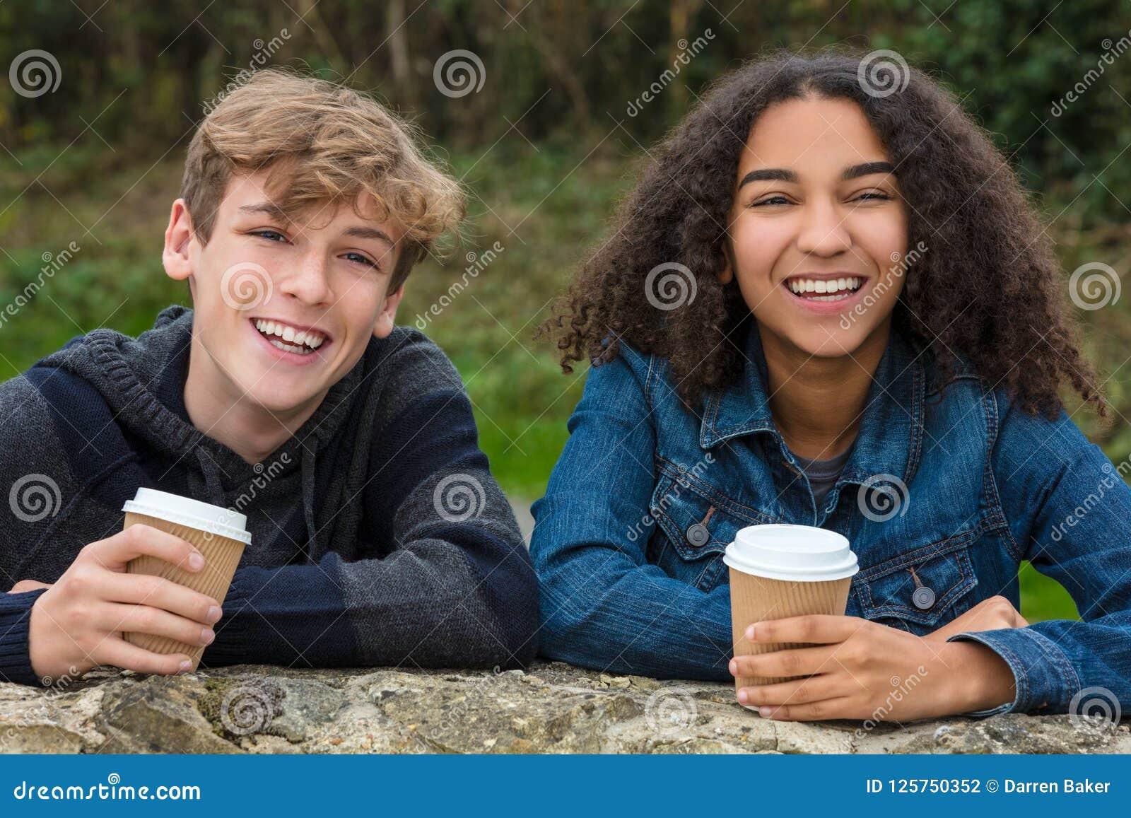Adolescents garçon de métis et café potable de fille d Afro-américain