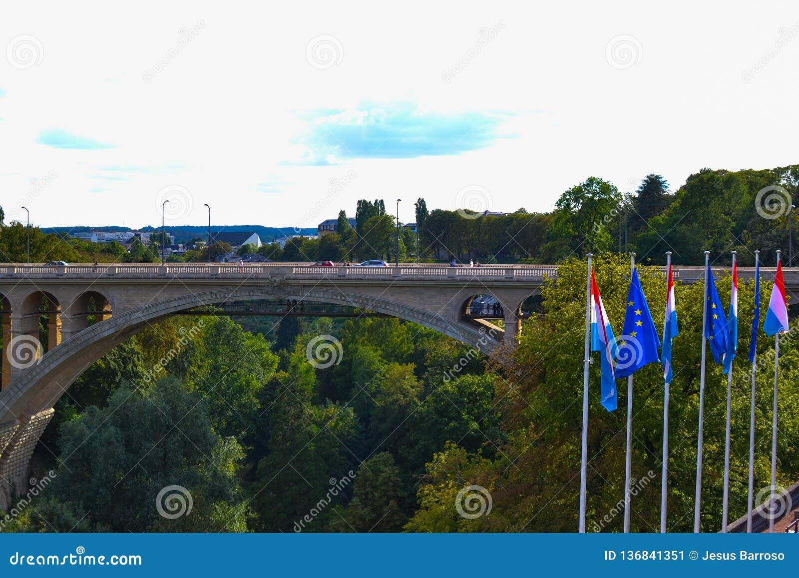Adolphe Bridge Pont Adolphe i den Luxembourg staden, Luxembourg, med gröna träd och flaggor av Luxembourg och Europa på