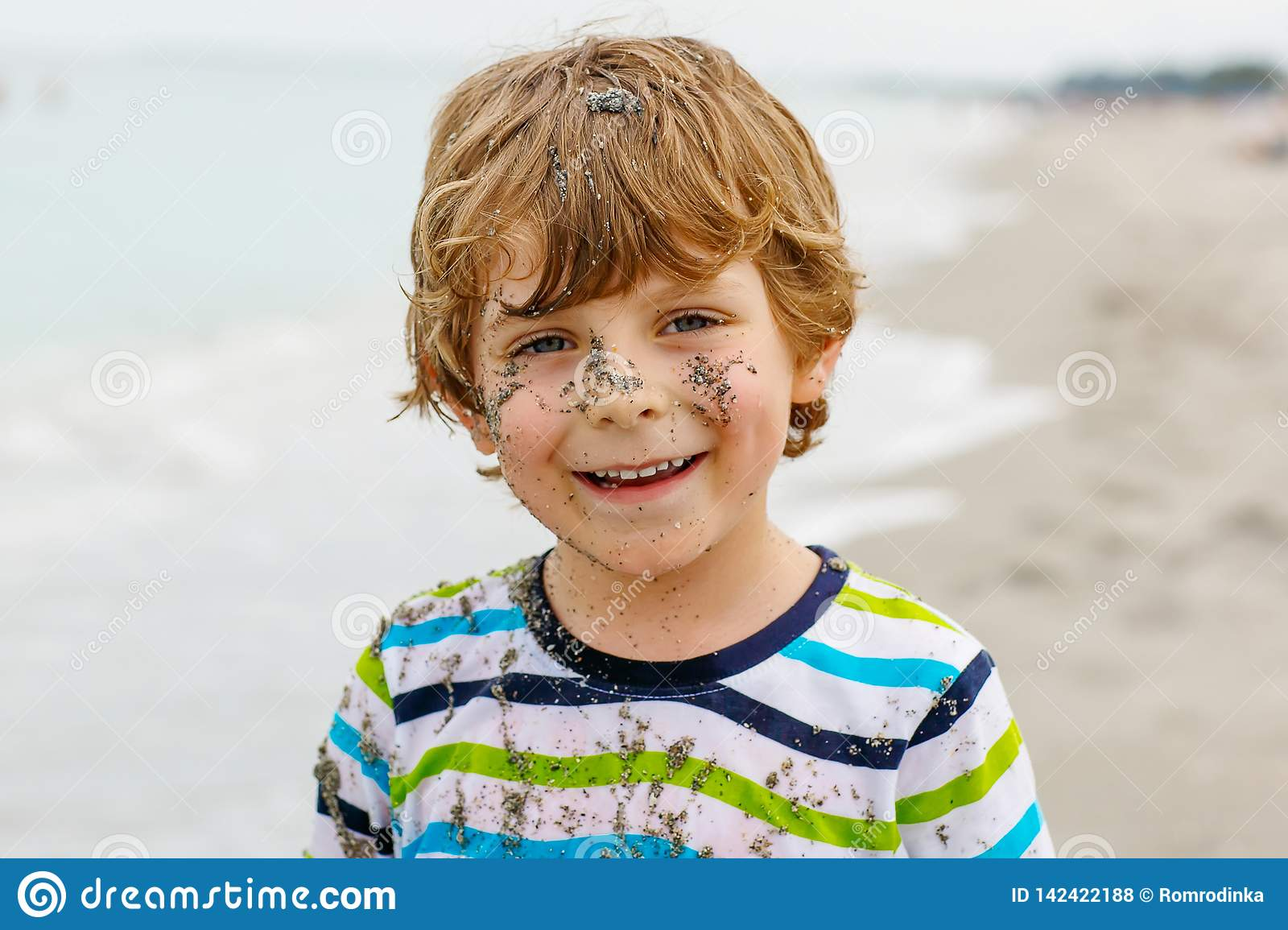 Adorable active little kid boy having fun on beach of North Sea in Germany. Happy cute child relaxing, playing and