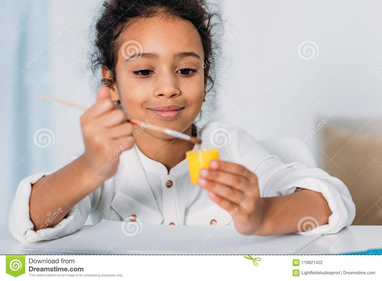 adorable african american kid putting paint brush into