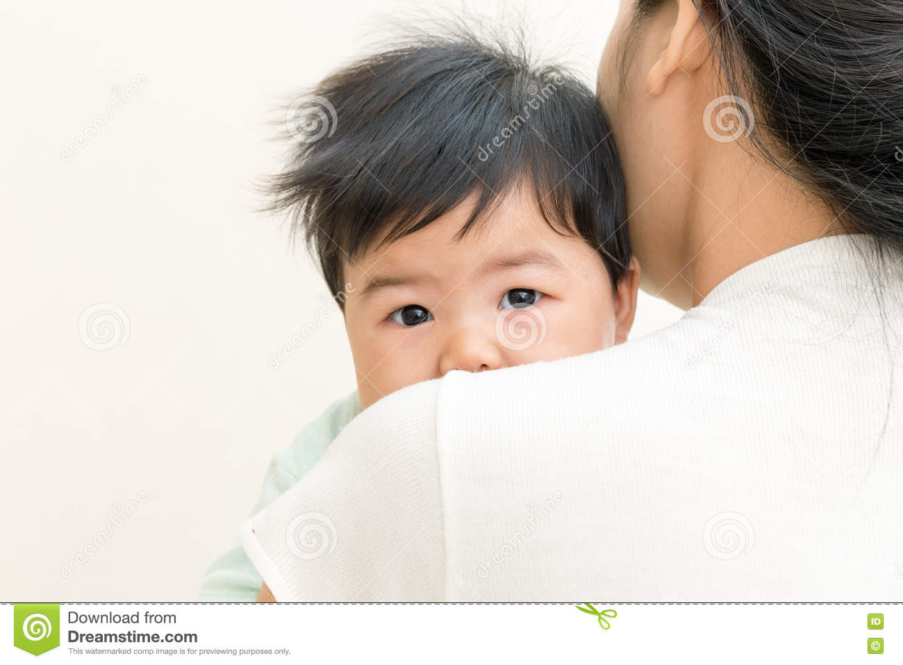 Adorable asian baby sick and unhappy on mom shoulder.