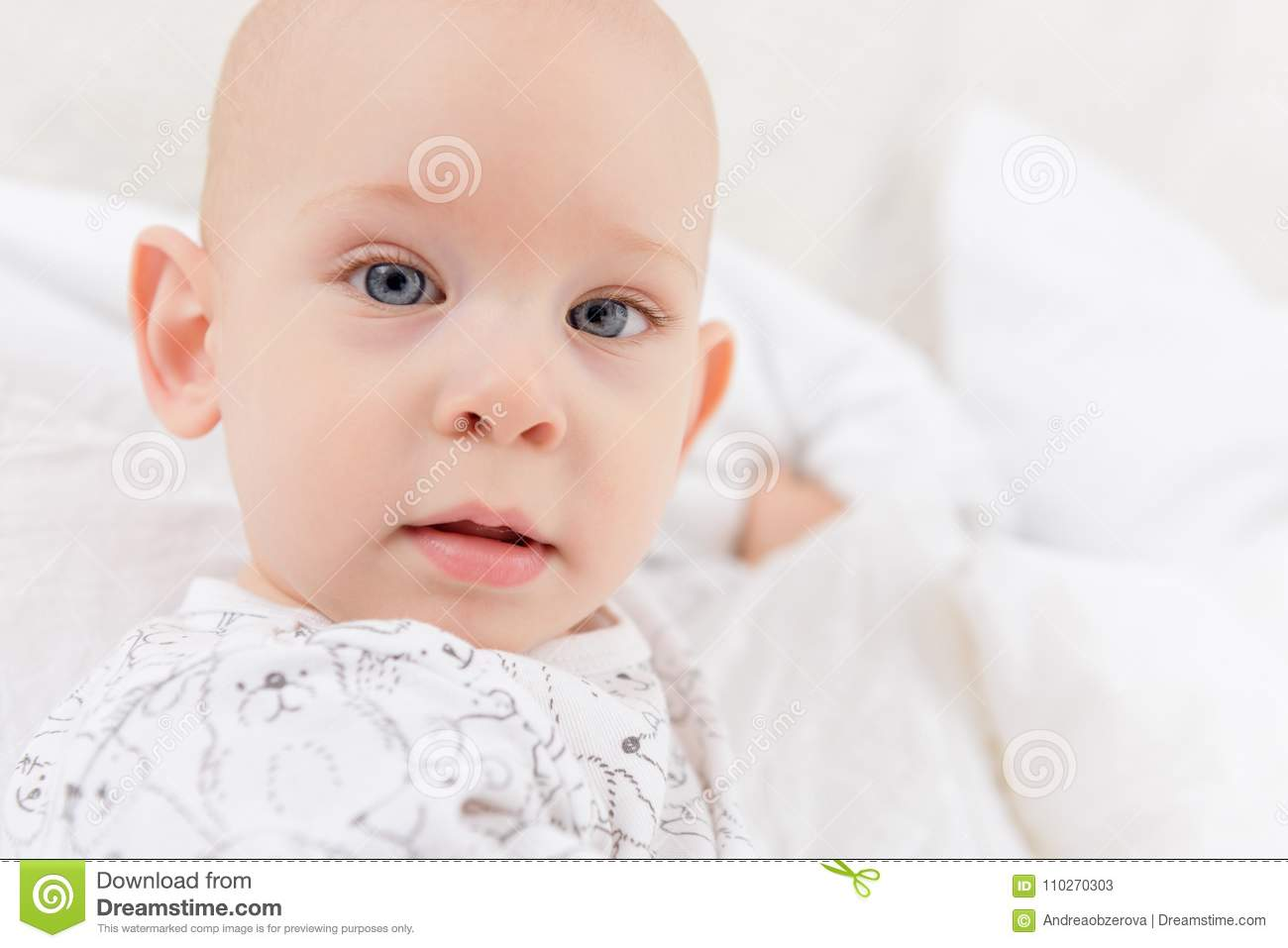 Adorable baby boy with blue eyes looking directly at camera trying to reach for it. Cute toddler close up.
