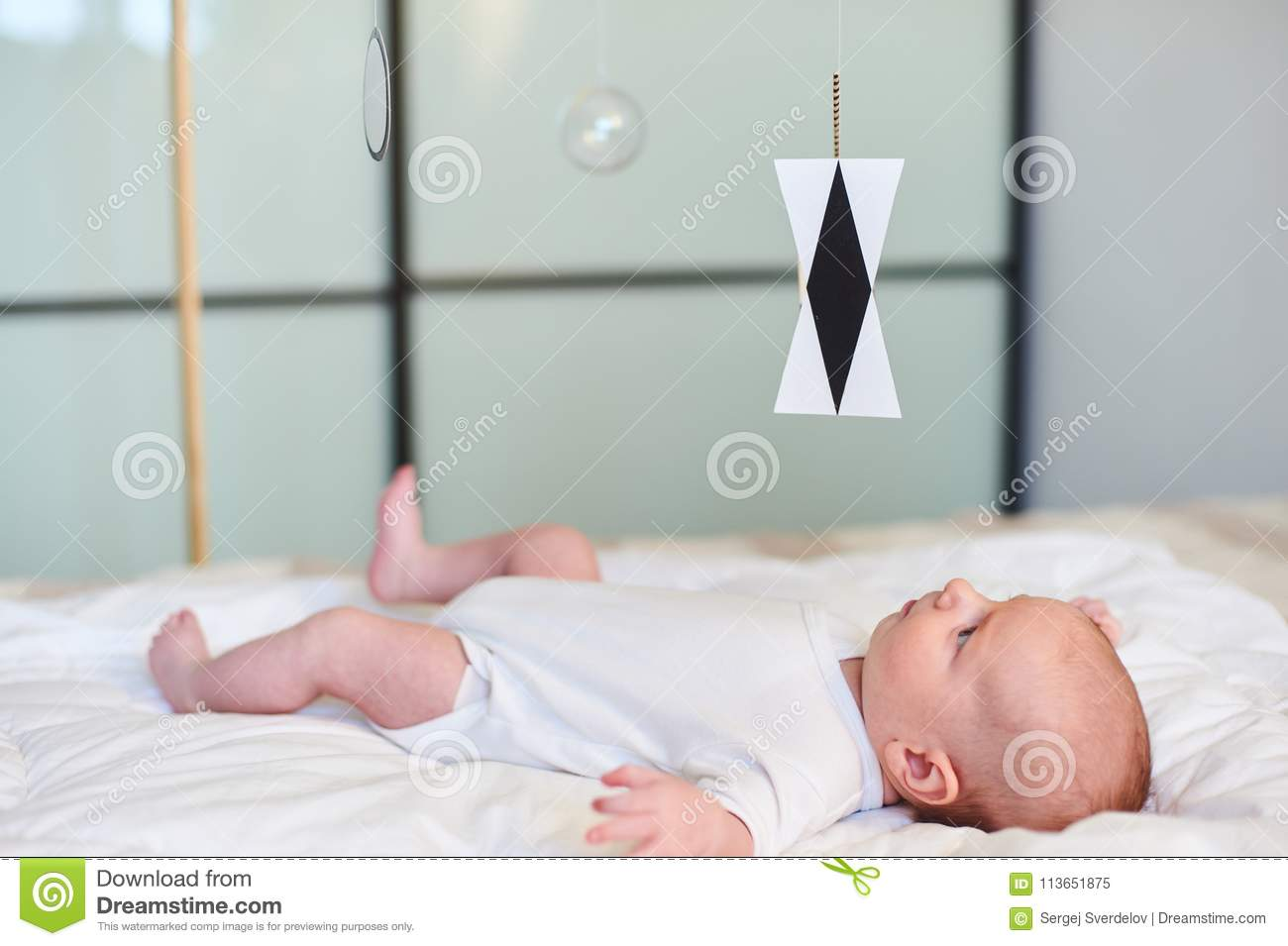 Adorable baby boy in white sunny bedroom lying and looks at Munari Montessori mobile.