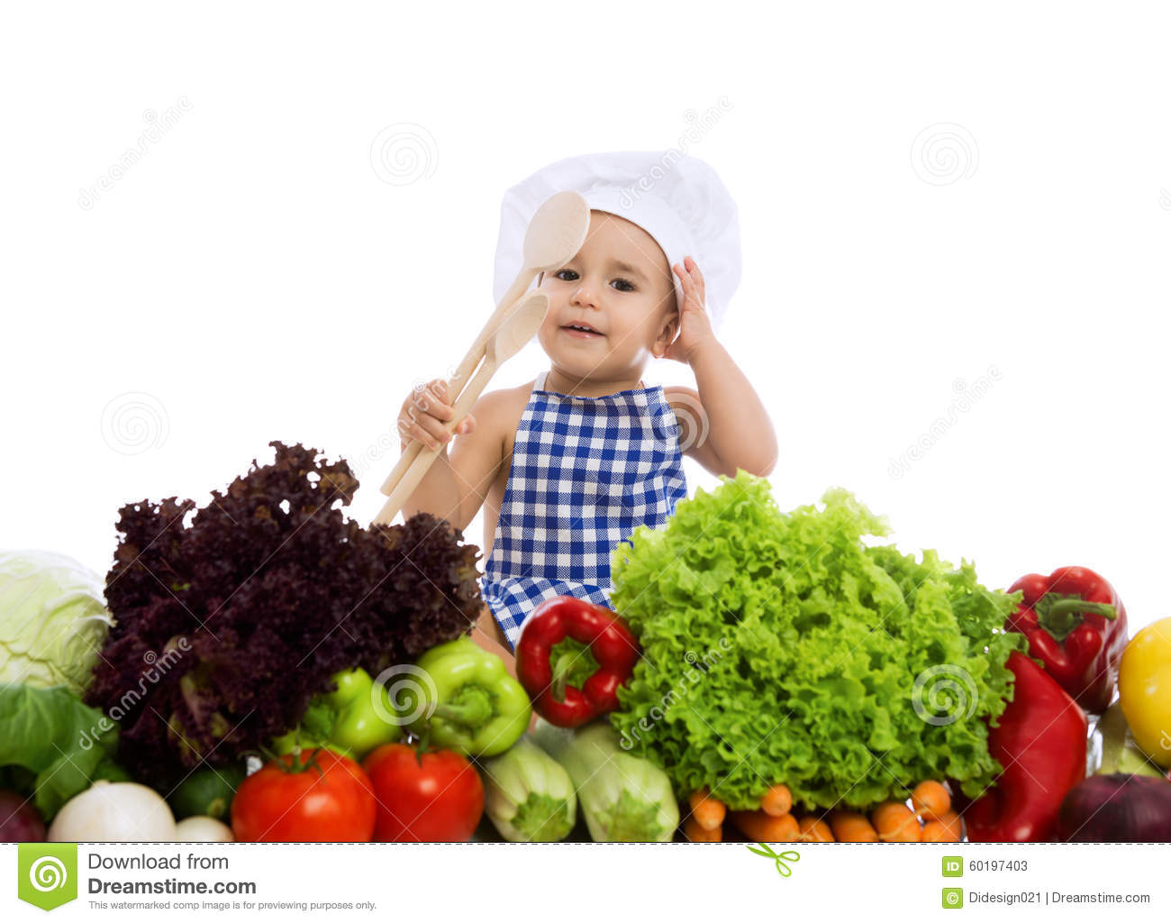 Adorable baby chef with healthy food vegetables and holding scoo