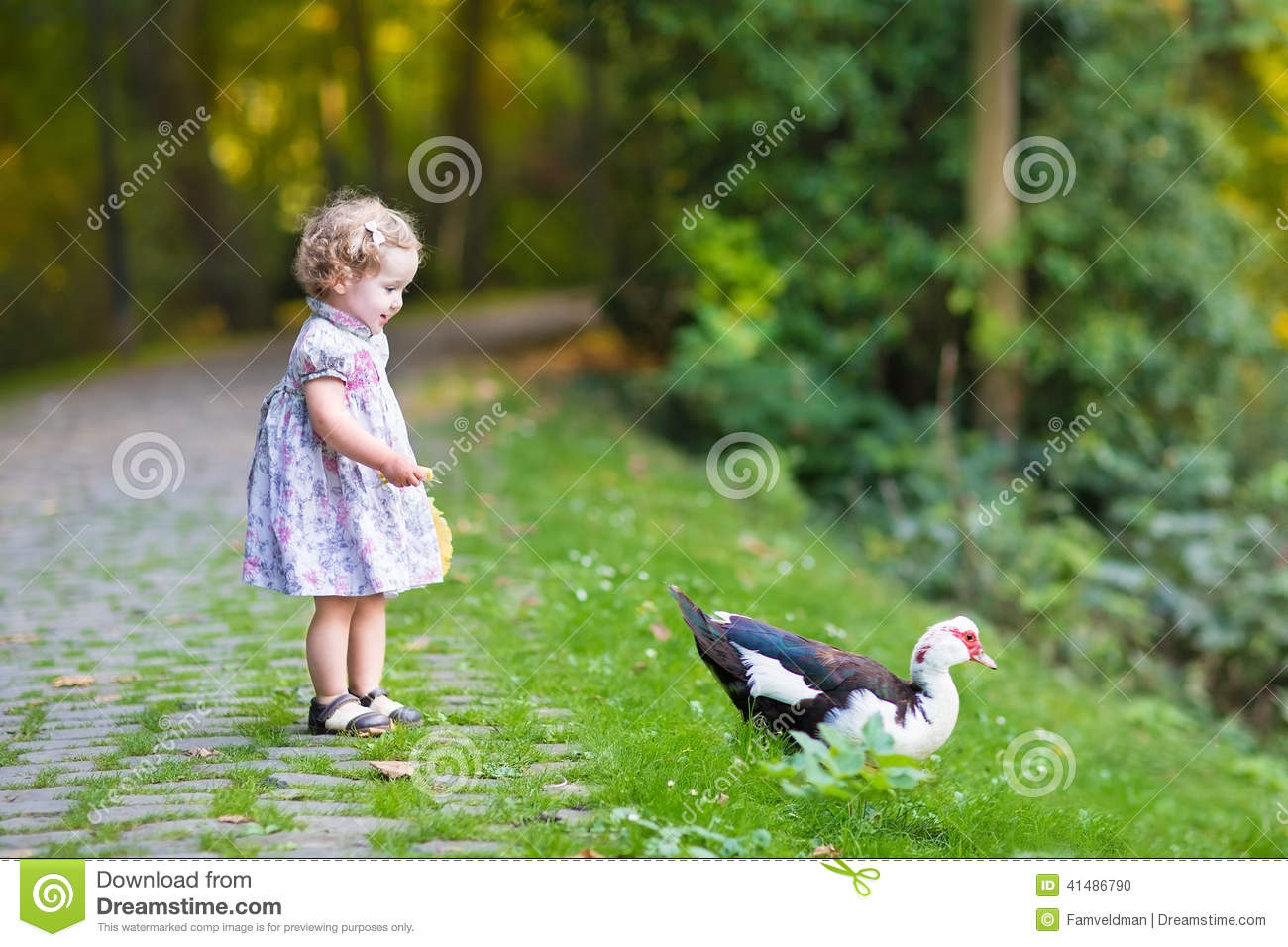 Adorable baby girl in festive dress with wild duck