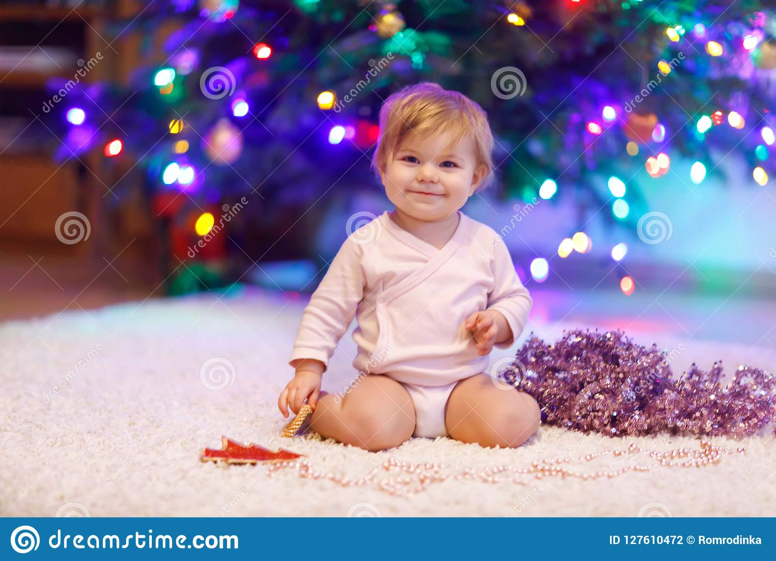 c866636b36b Adorable baby girl holding pink Christmas tree beads in cute hands. Little  child playing and decorating xmas tree with family. First celebration.