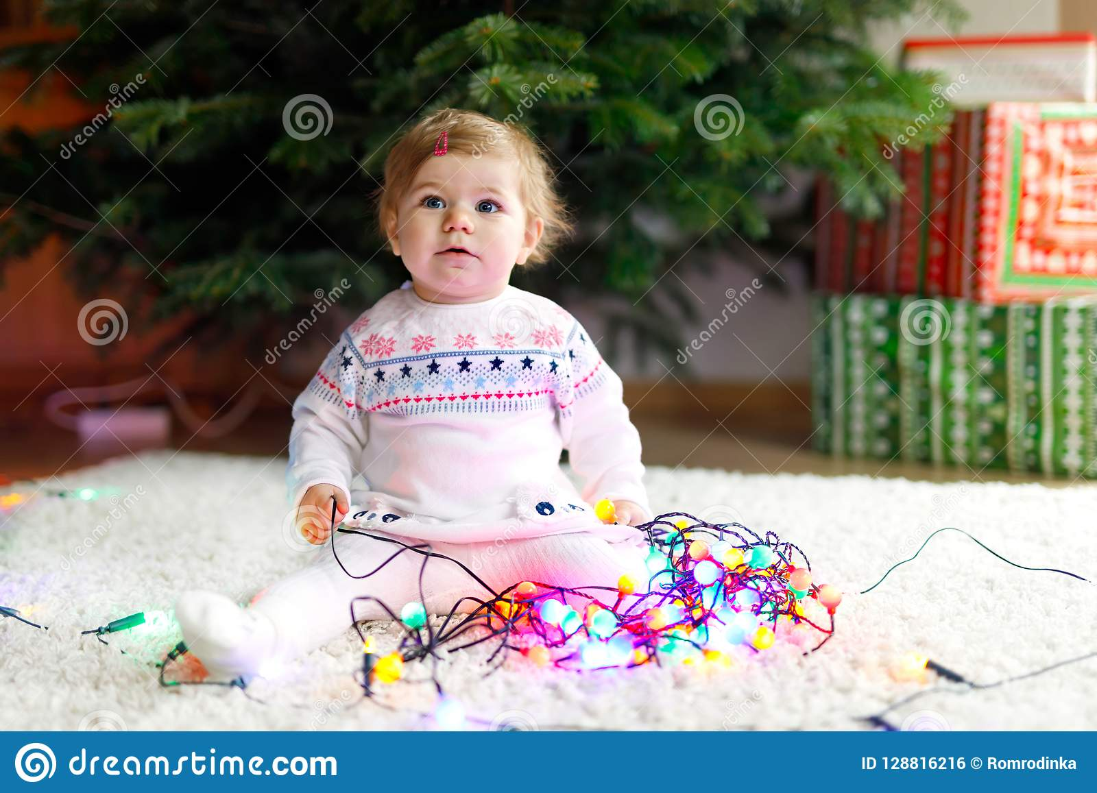 91c4d04bdb37 Adorable baby girl holding colorful lights garland in cute hands. Little  child in festive clothes decorating Christmas tree with family.